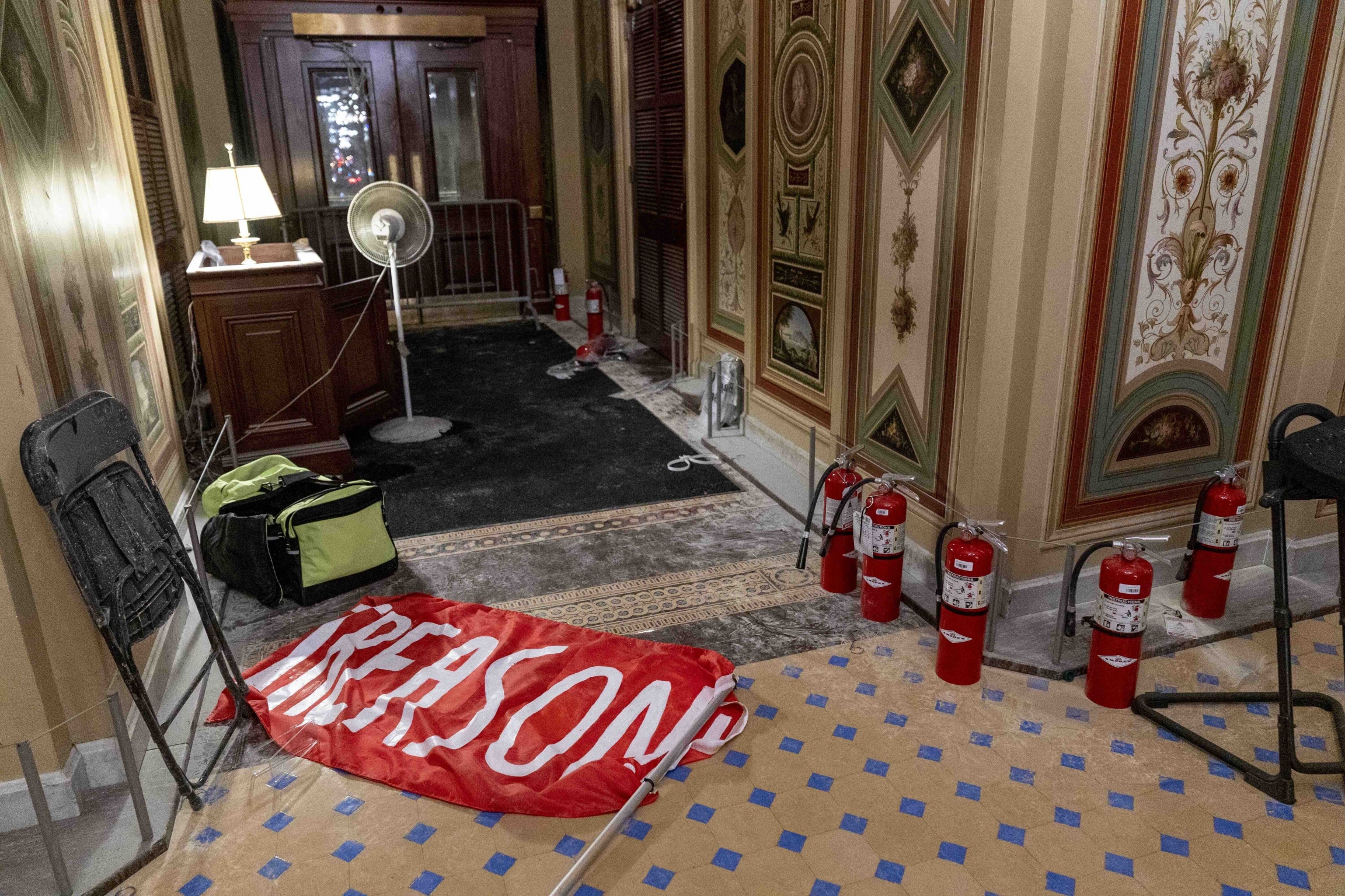 """A flag that reads """"Treason"""" is visible on the ground of the US Capitol building."""