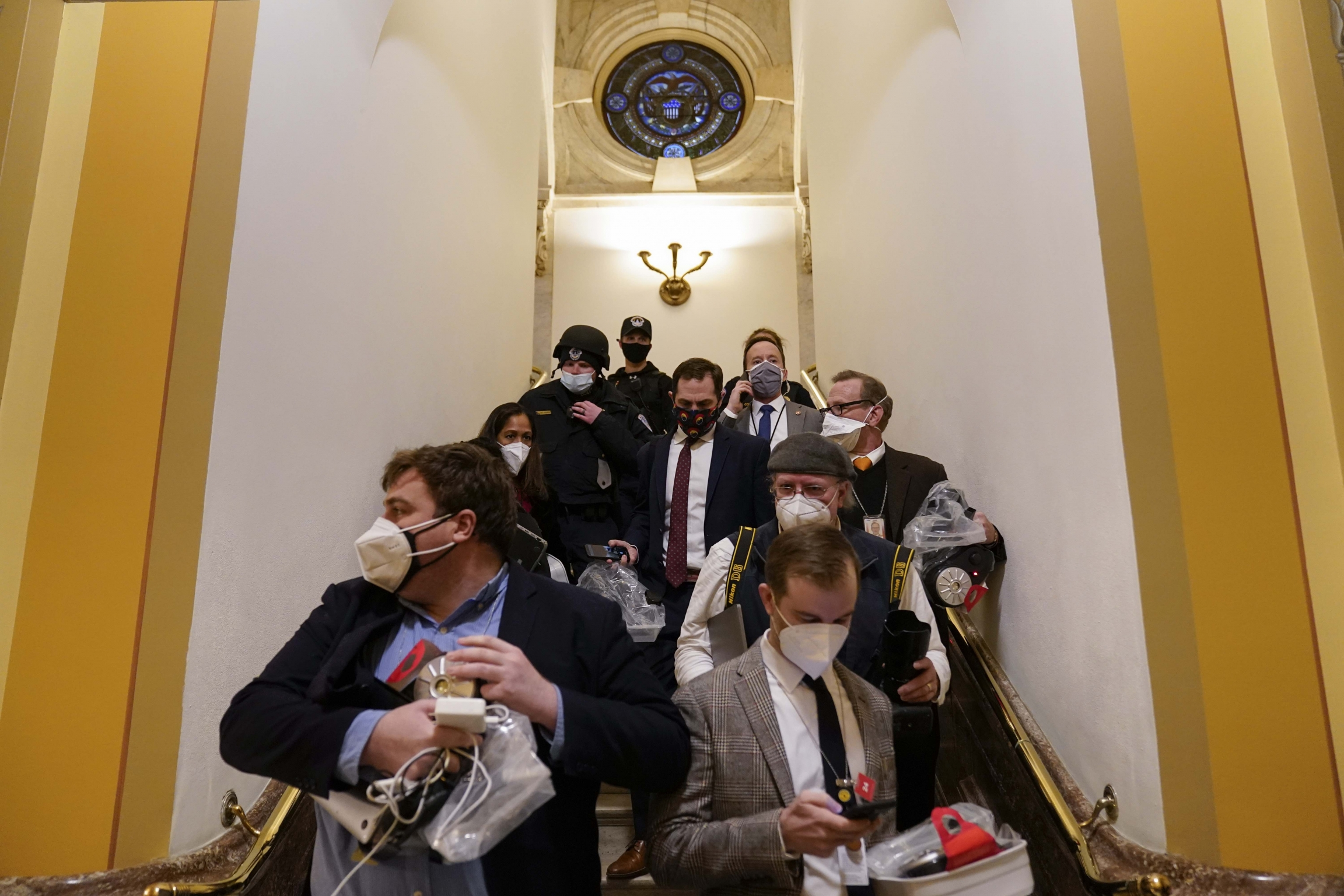 People evacuate from the House chamber as a violent mob of Trump supporterstry to break in at the US Capitol on Wednesday, Jan. 6, 2021, in Washington, DC.