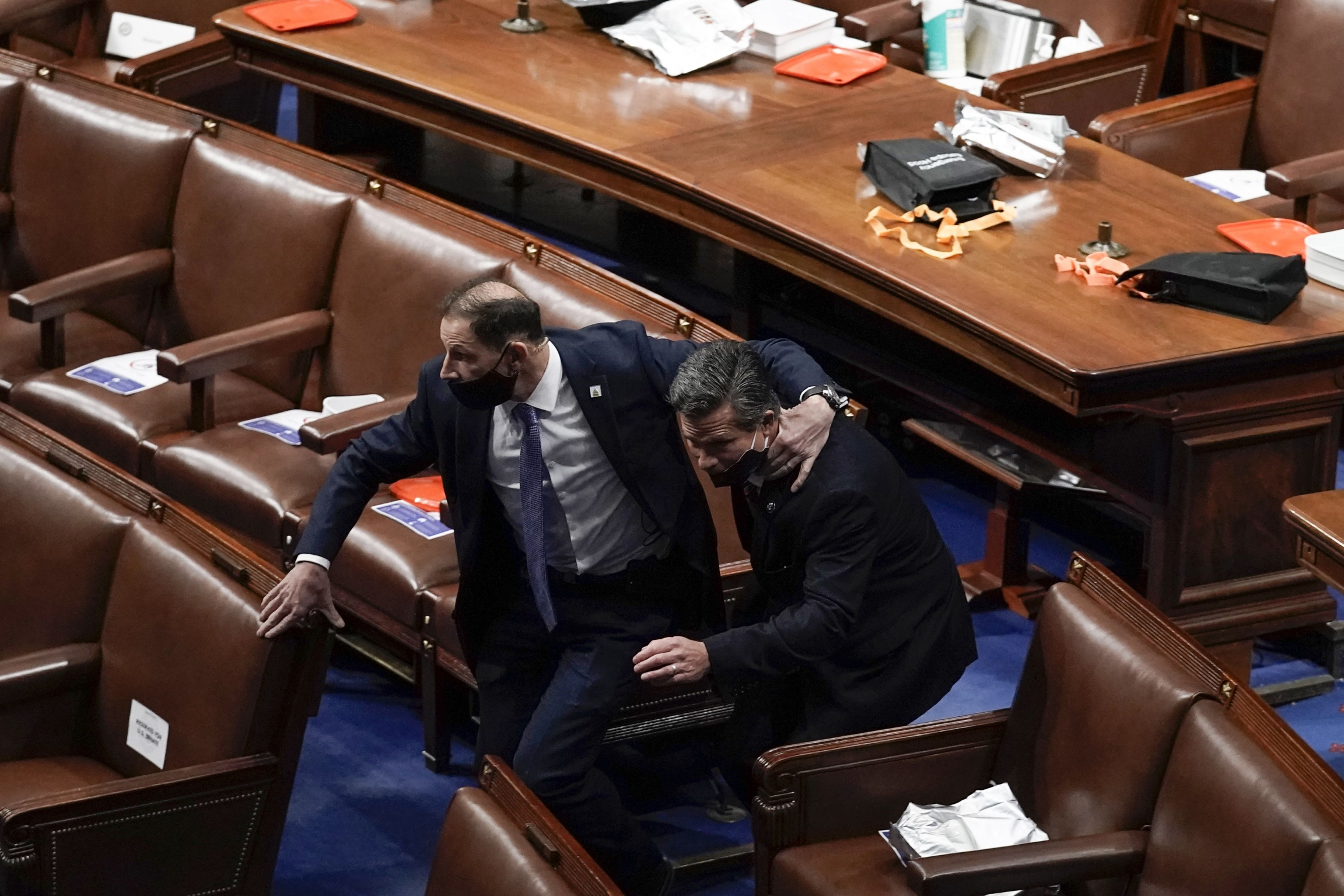 Two men in black suits run to evacuate the floor as a violent mobtriesto break into the House Chamber at the USCapitol