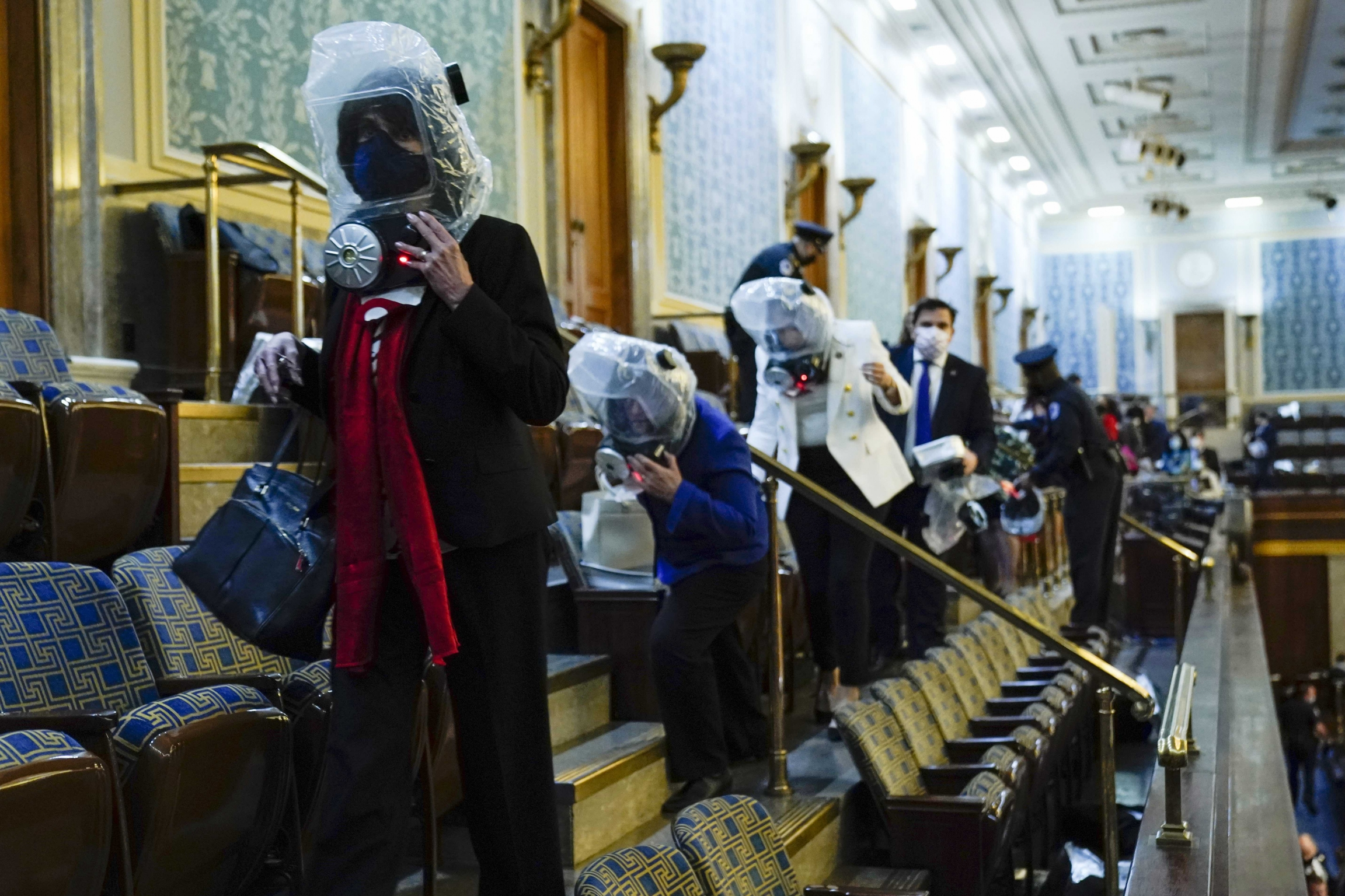 People wearing plastic protection around their heads shelter in the House gallery as a mob of Trump supporters try to break into the House chamber at the US Capitol on Wednesday, Jan. 6, 2021, in Washington, DC.