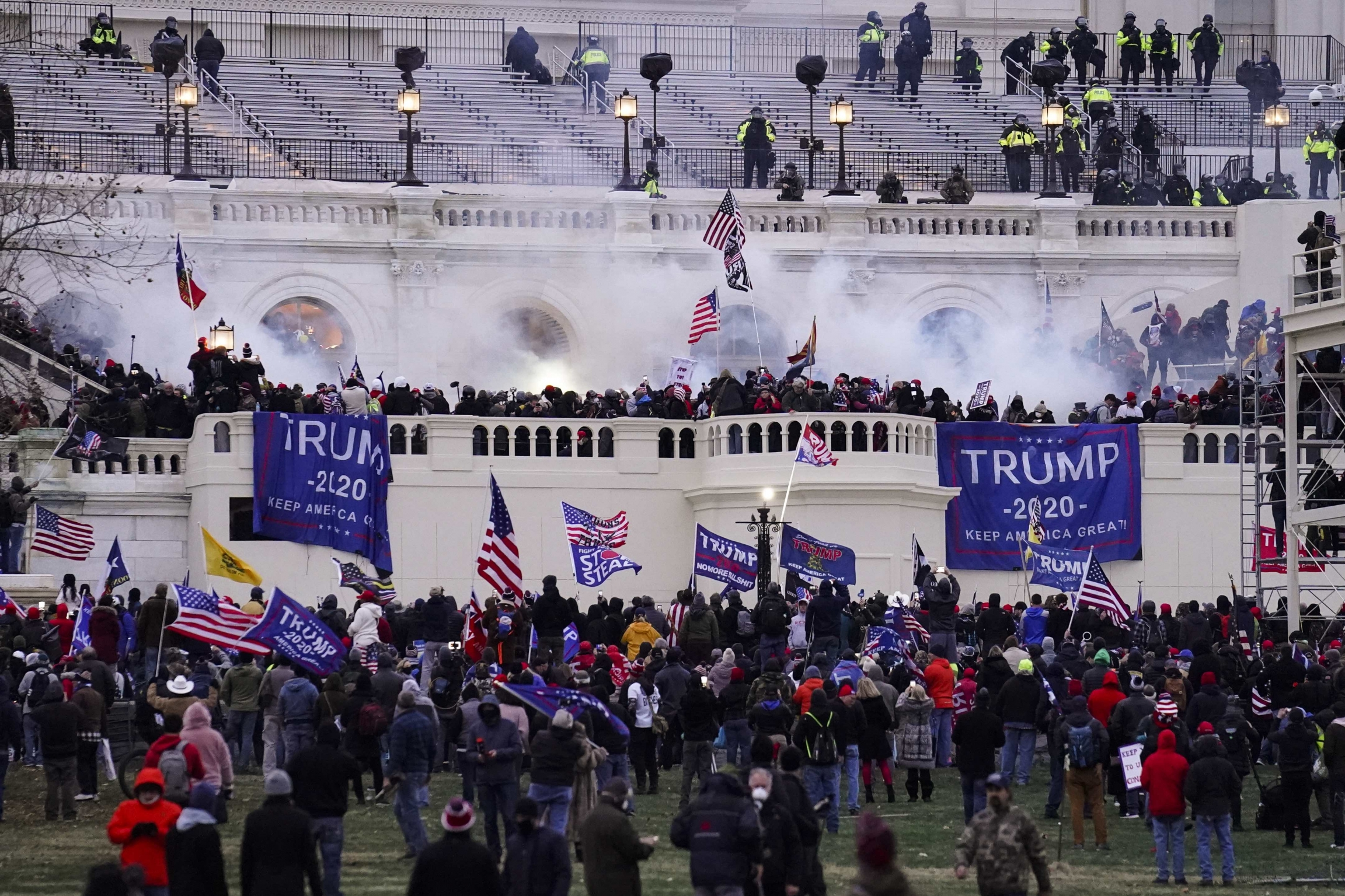 A large group of people with flags that read Tump storm the US Capitol building.
