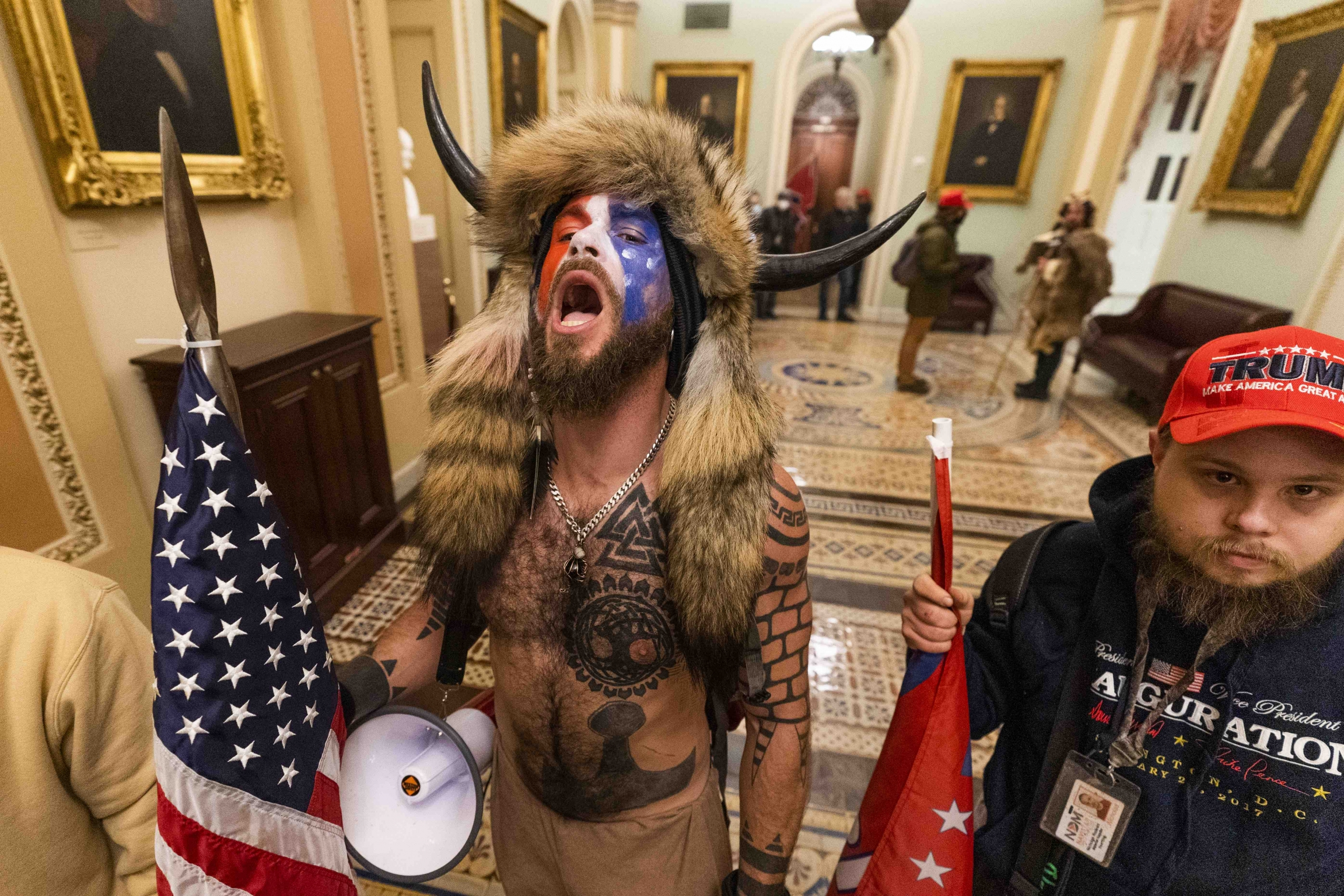 A supporter of President Donald Trump wearing horns and animal skins on his head chants outside the Senate chamber inside the Capitol, Wednesday, Jan. 6, 2021, in Washington, DC.