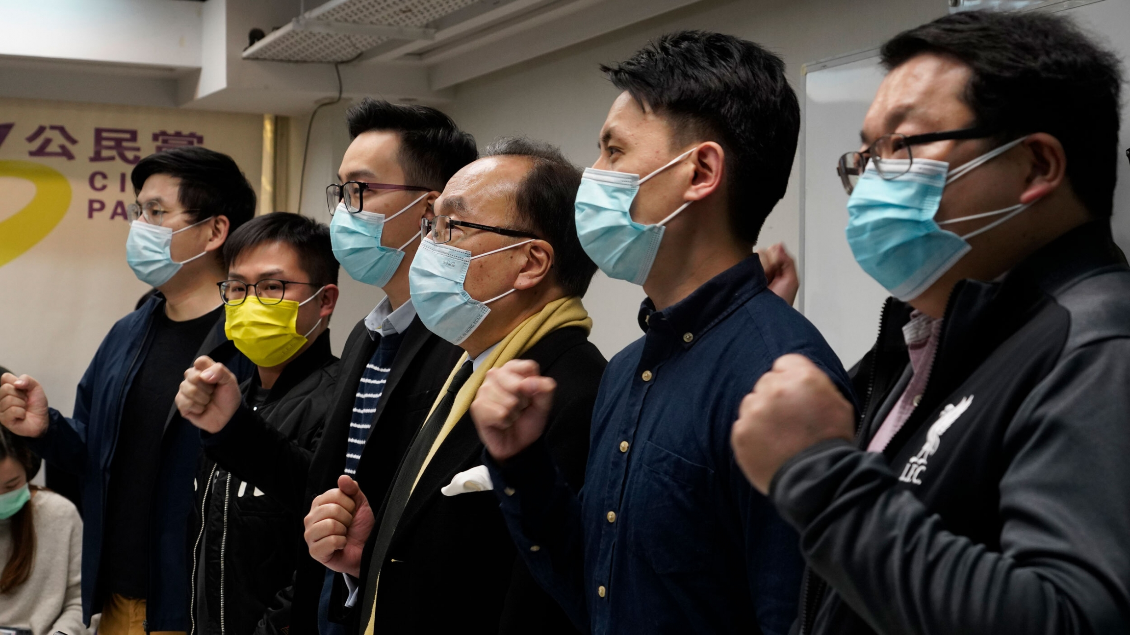 Six people wearing medical masks stand and shout slogans.