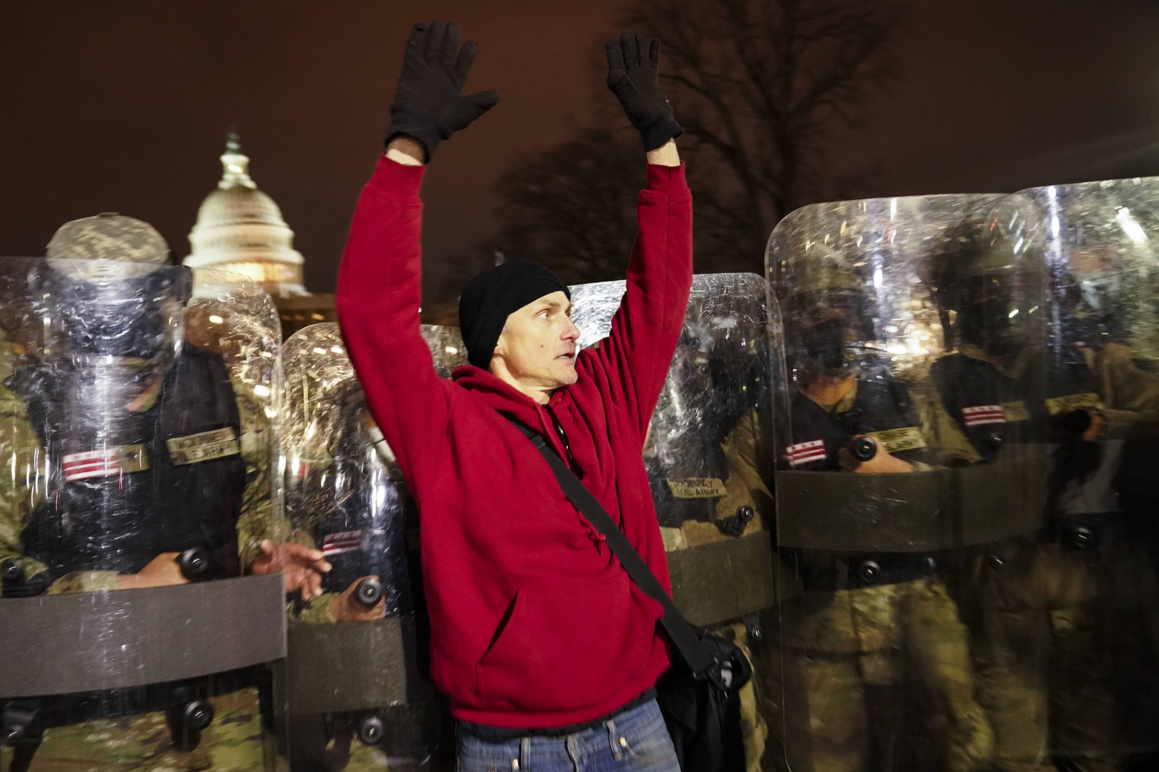 National guard appear behind a man wearing a red sweater, who has his hands up.