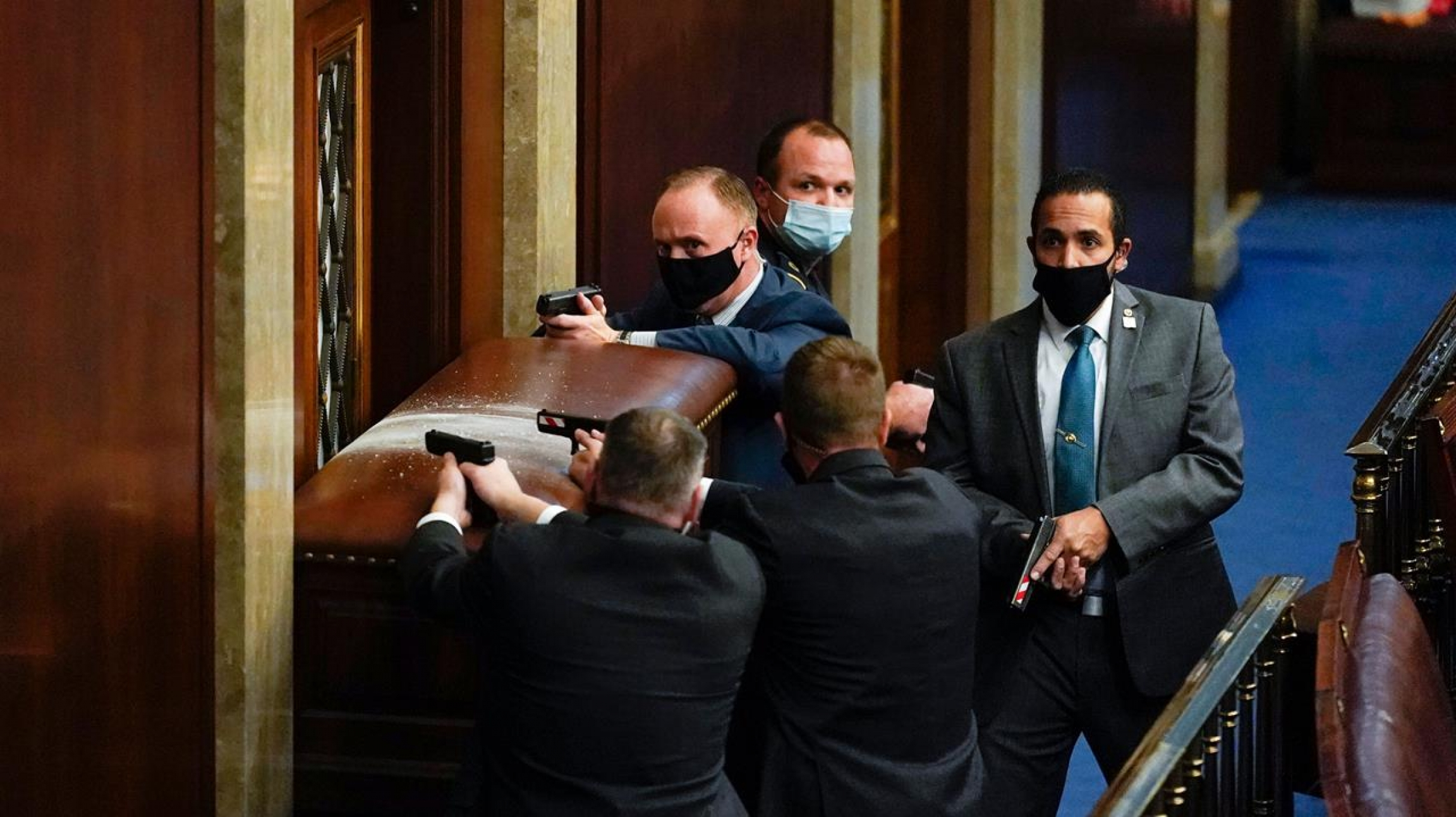 US Capitol police with guns drawn stand near a barricaded door as members of a mob try to break into the House Chamber in Washington.