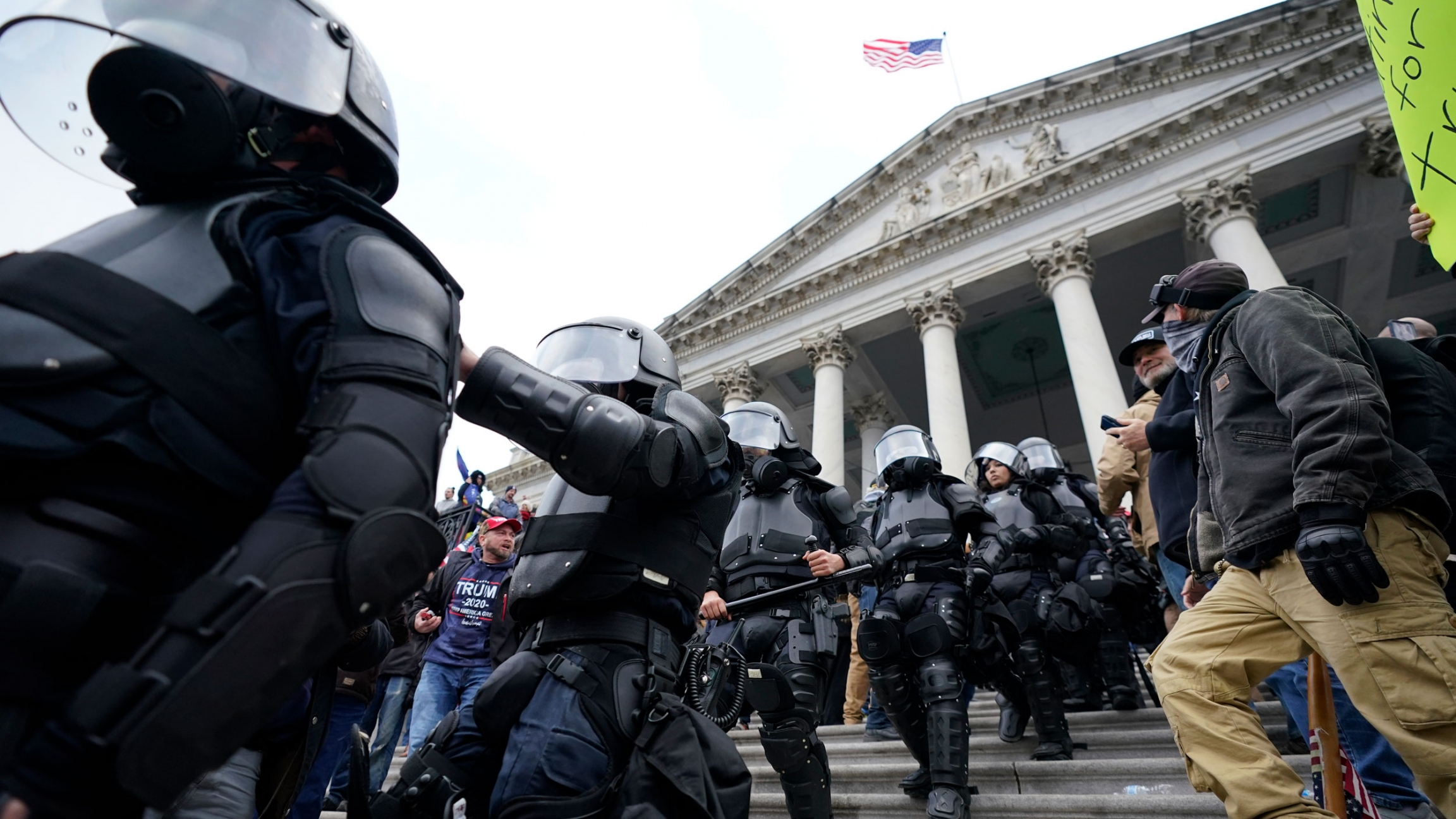 A line of police are shown walking down the Capitol building staircase dressed in black armor with helmets.