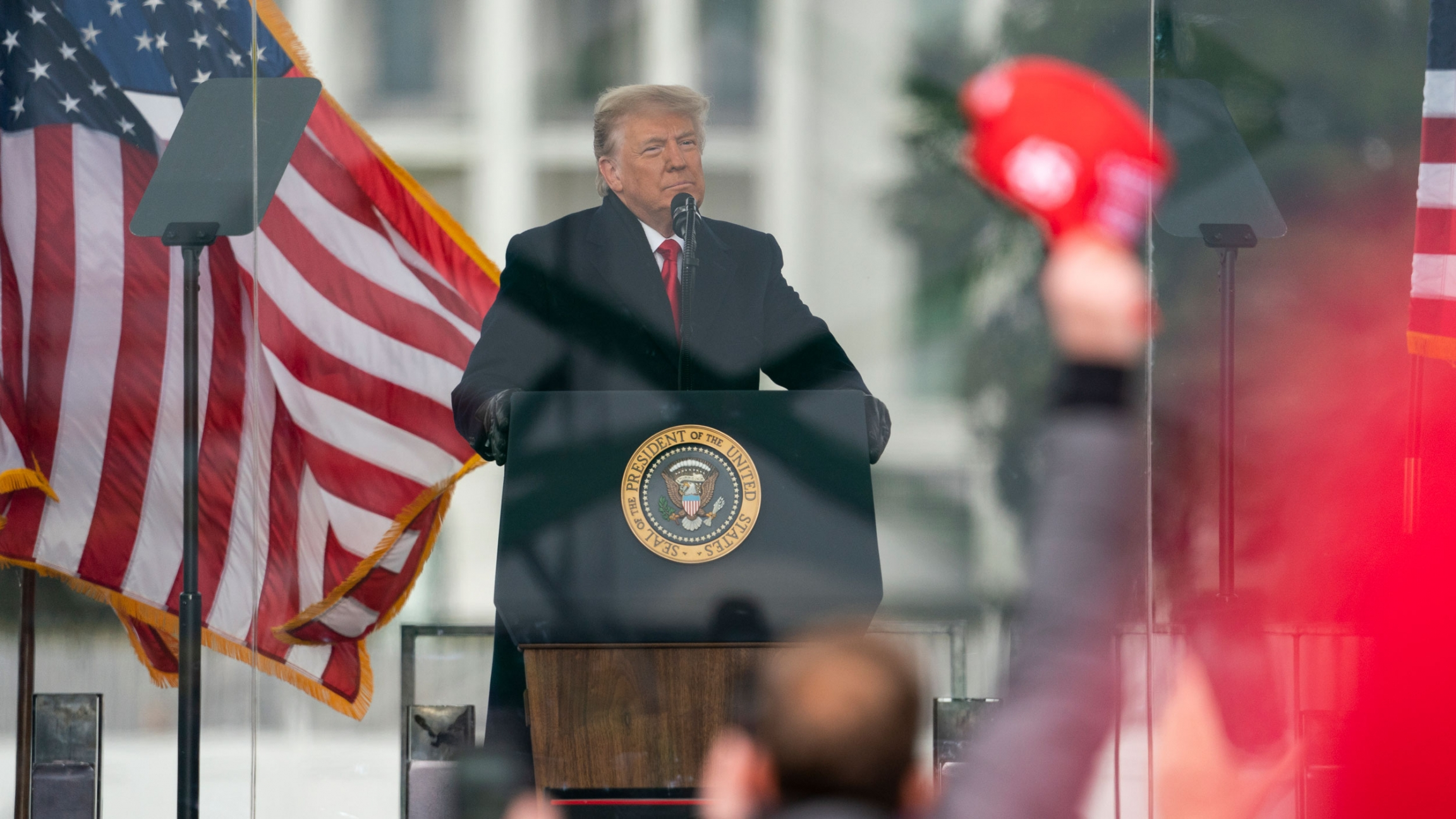 President Donald Trump is shown standing at a podium speaking with US flags waving behind him.