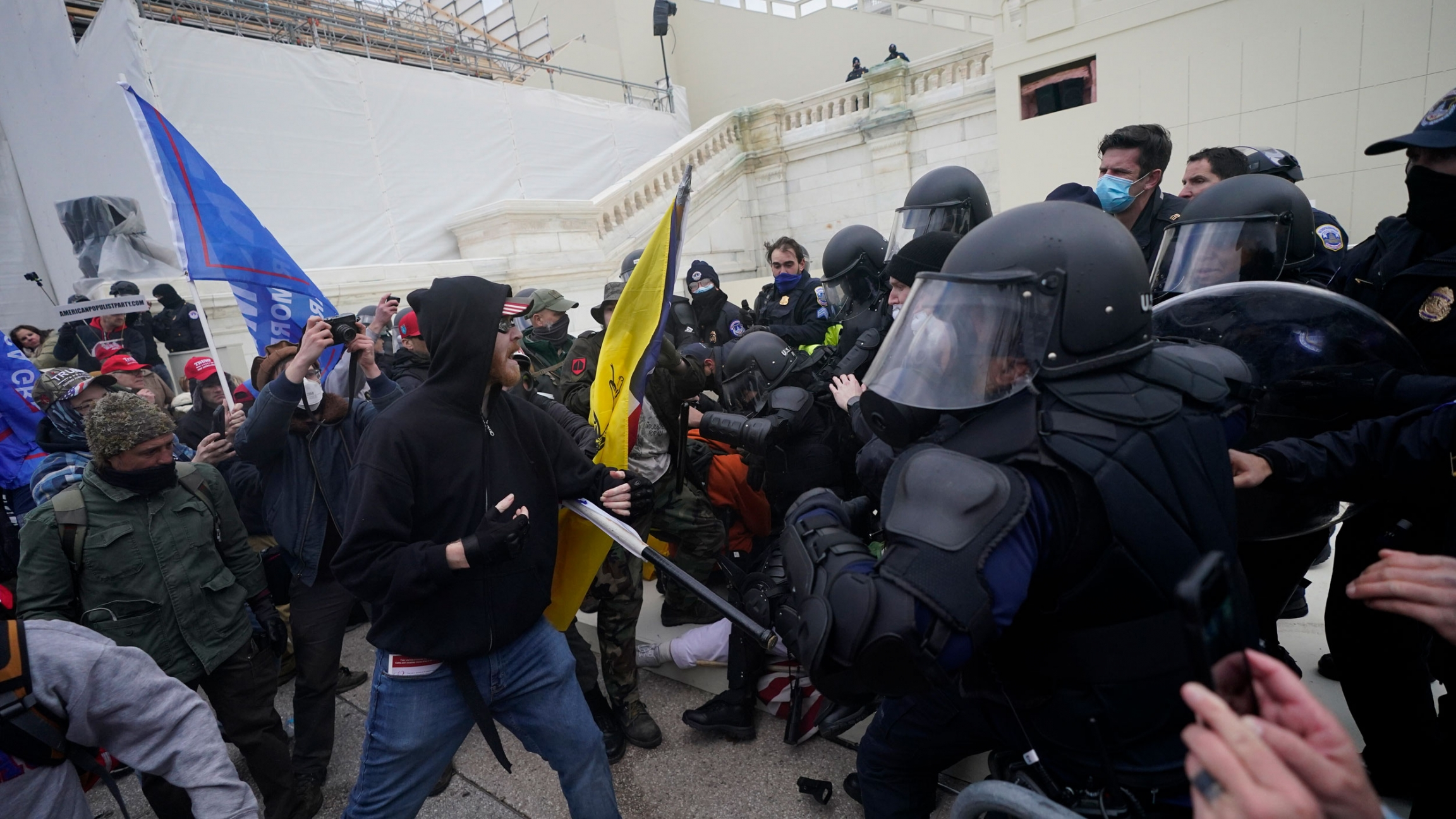 A large crowd of people are shown forcing their way past armed security officers at the US Capitol building.
