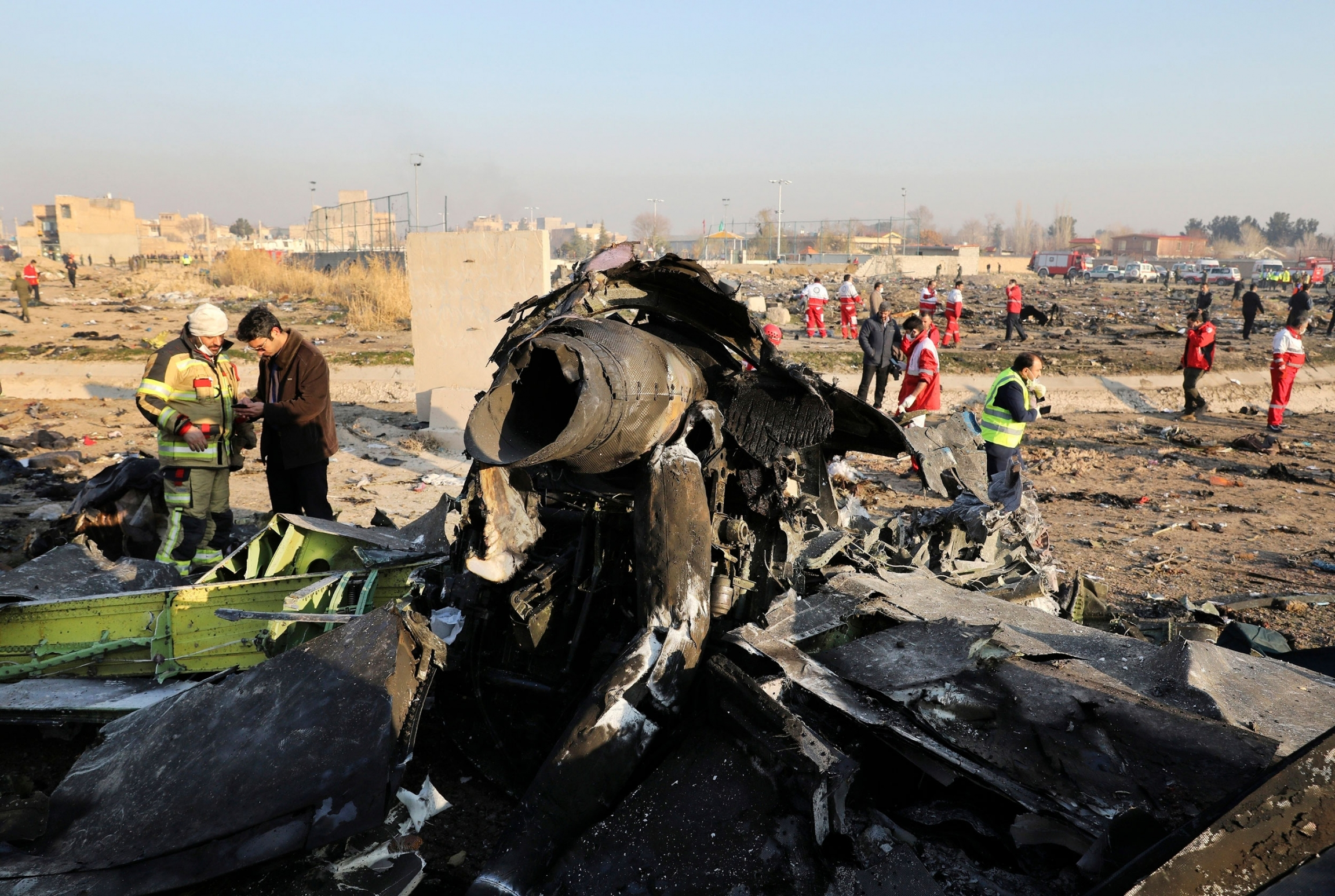 The charred remains of a passenger aircraft is shown with several inspectors shown on the scene in the distance.