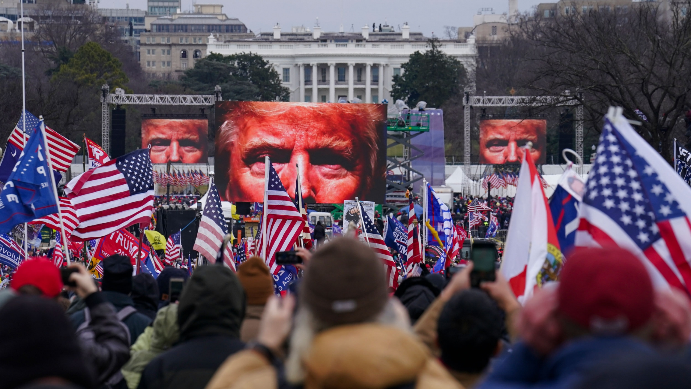 A large crowd of people are shown holding small US flags with screens showing Donald Trump's eyes in the distance.
