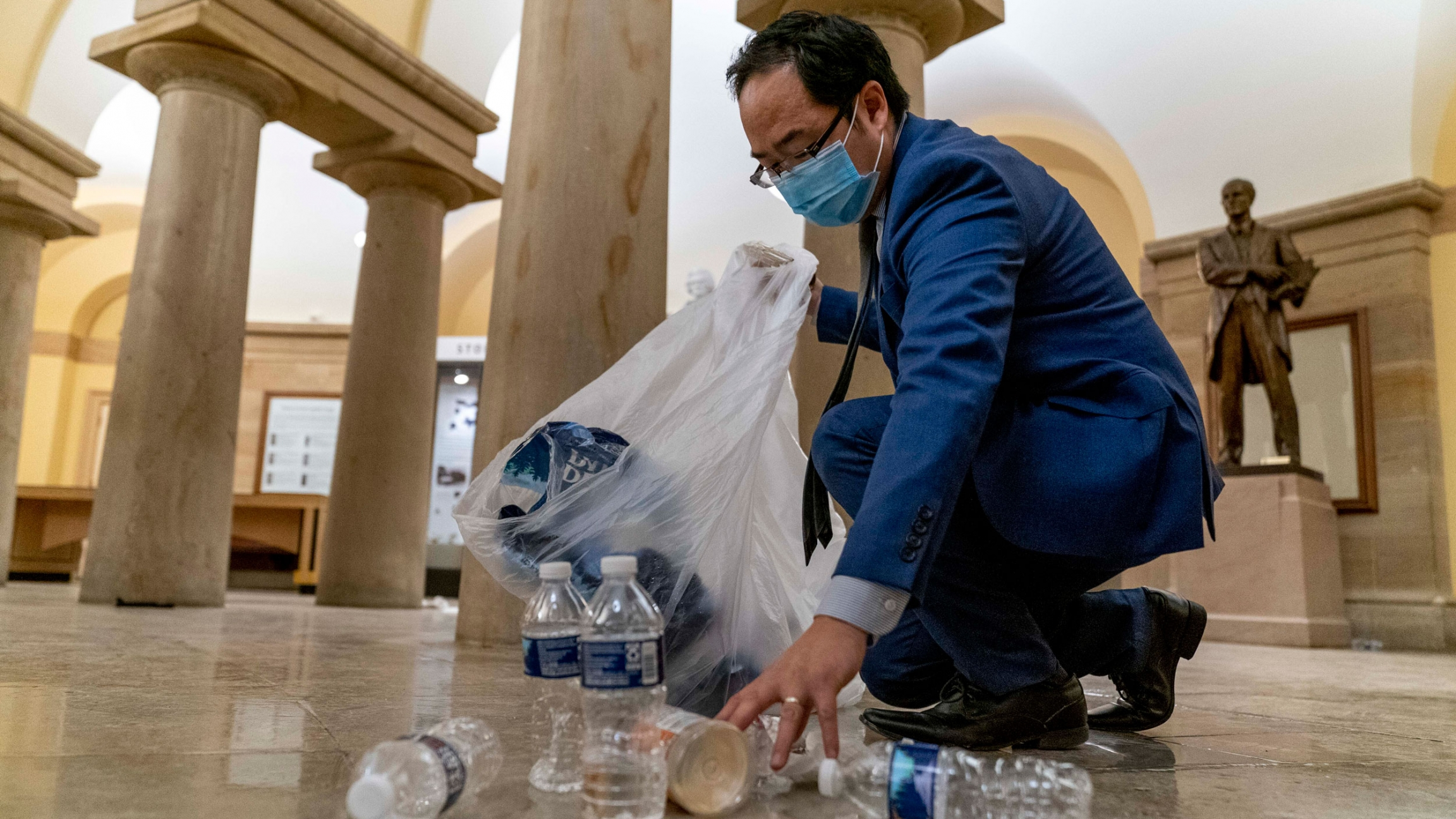 Rep. Andy Kim is shown kneeling and with a clear trash back helping clean up debris and trash strewn across the floor.