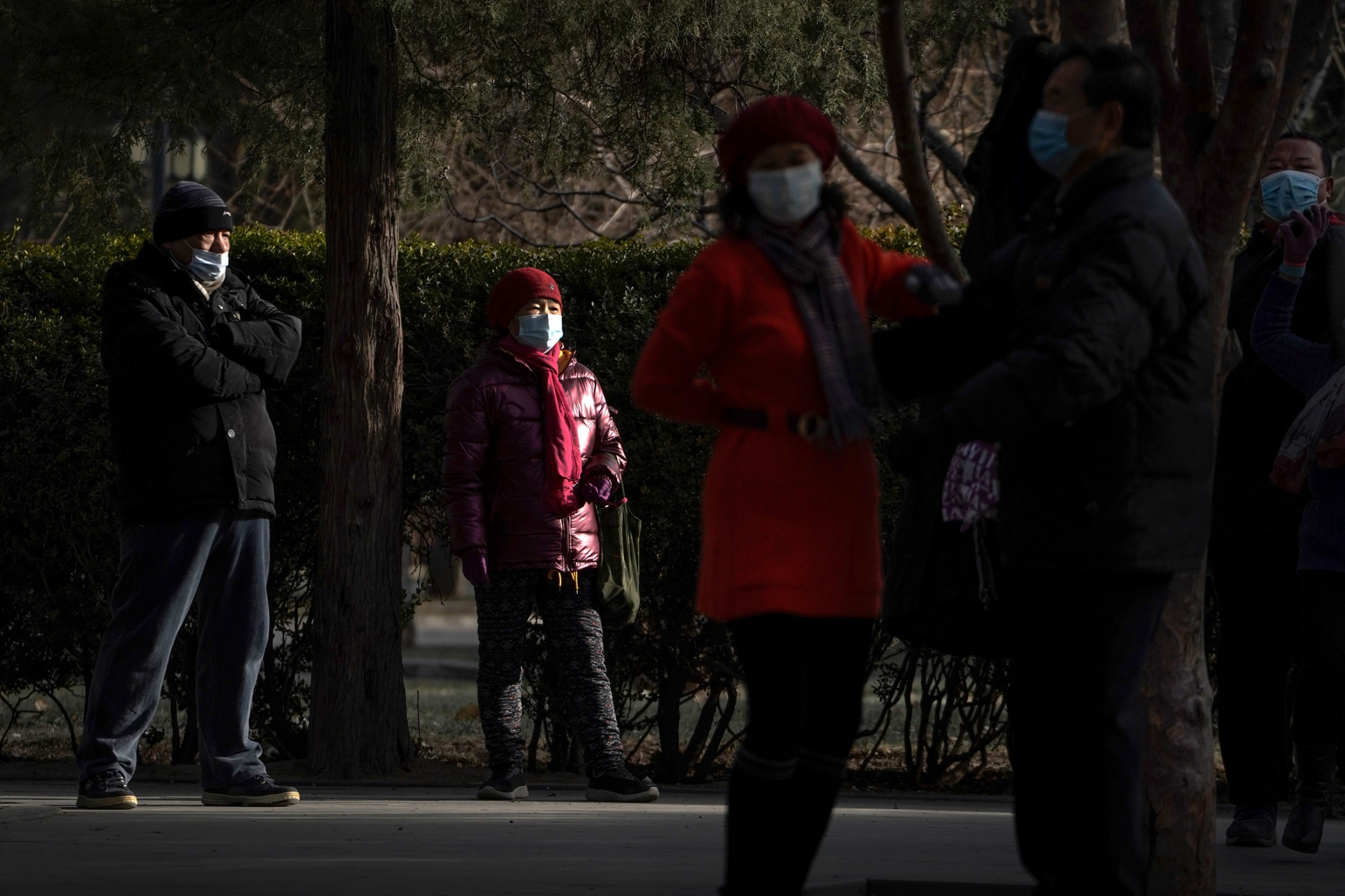 Several people are shown standing in a park and wearing face masks and winter jackes=ts.