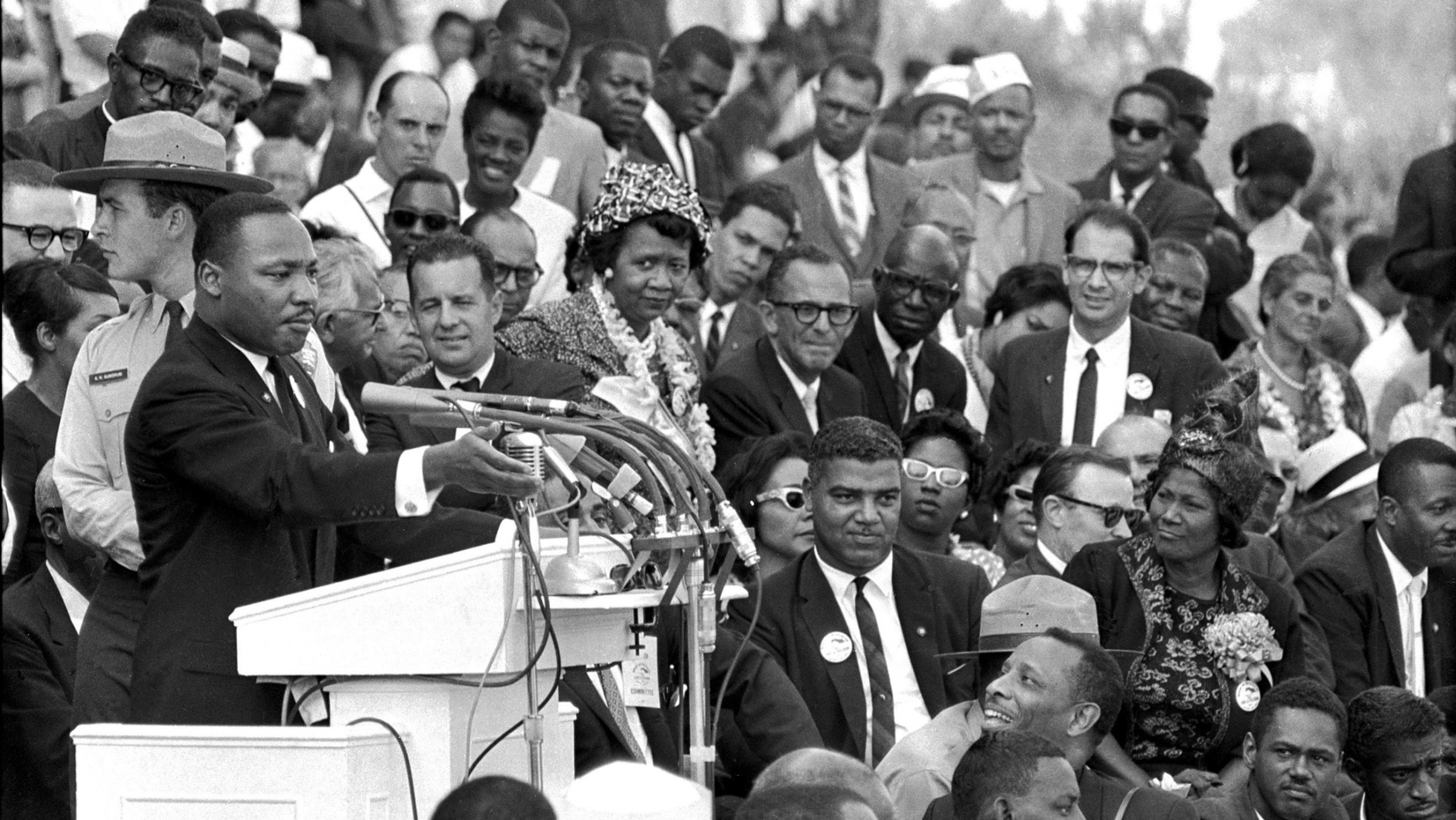 Rev. Dr. Martin Luther King Jr. is shown in a black and white photograph standing at a podium with several microphones and a crowd of people bedhind him.