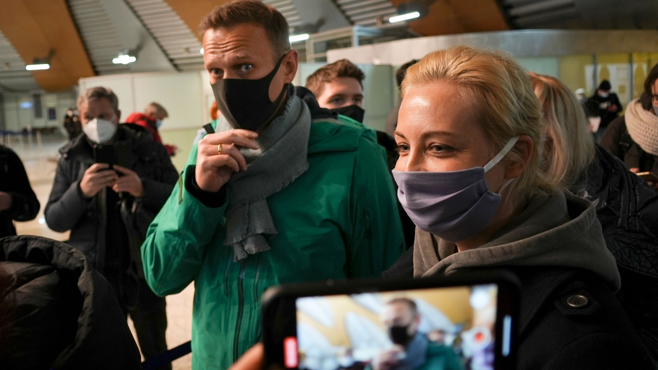 Alexei Navalny and his wife Yuliastand are shown wearing face masks and standing next to each other with a mobile phone also showing them in the near ground.