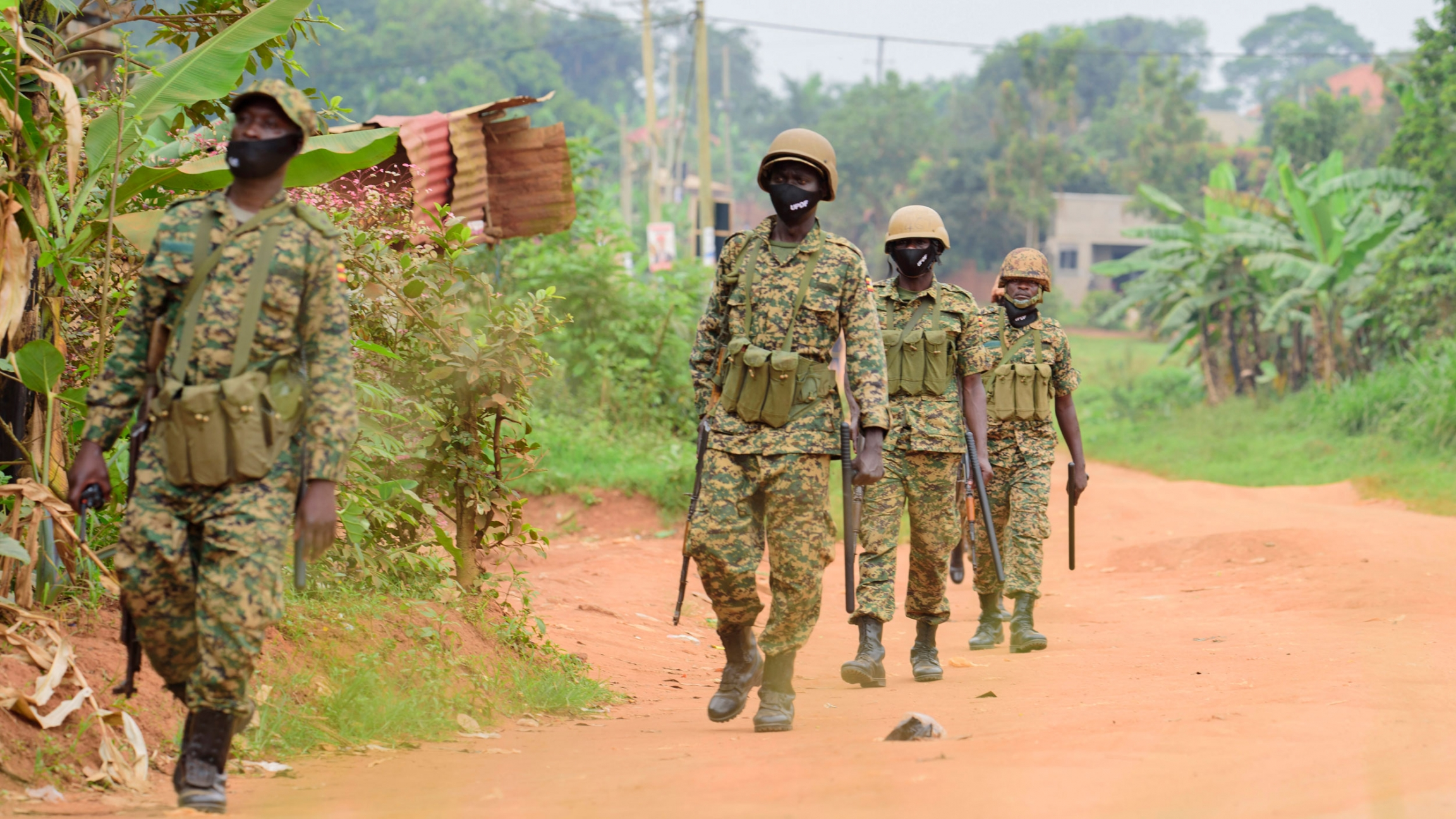 Four soldiers are shown wearing military fatigues and helmets while carrying weapons and walking in a dirt road.