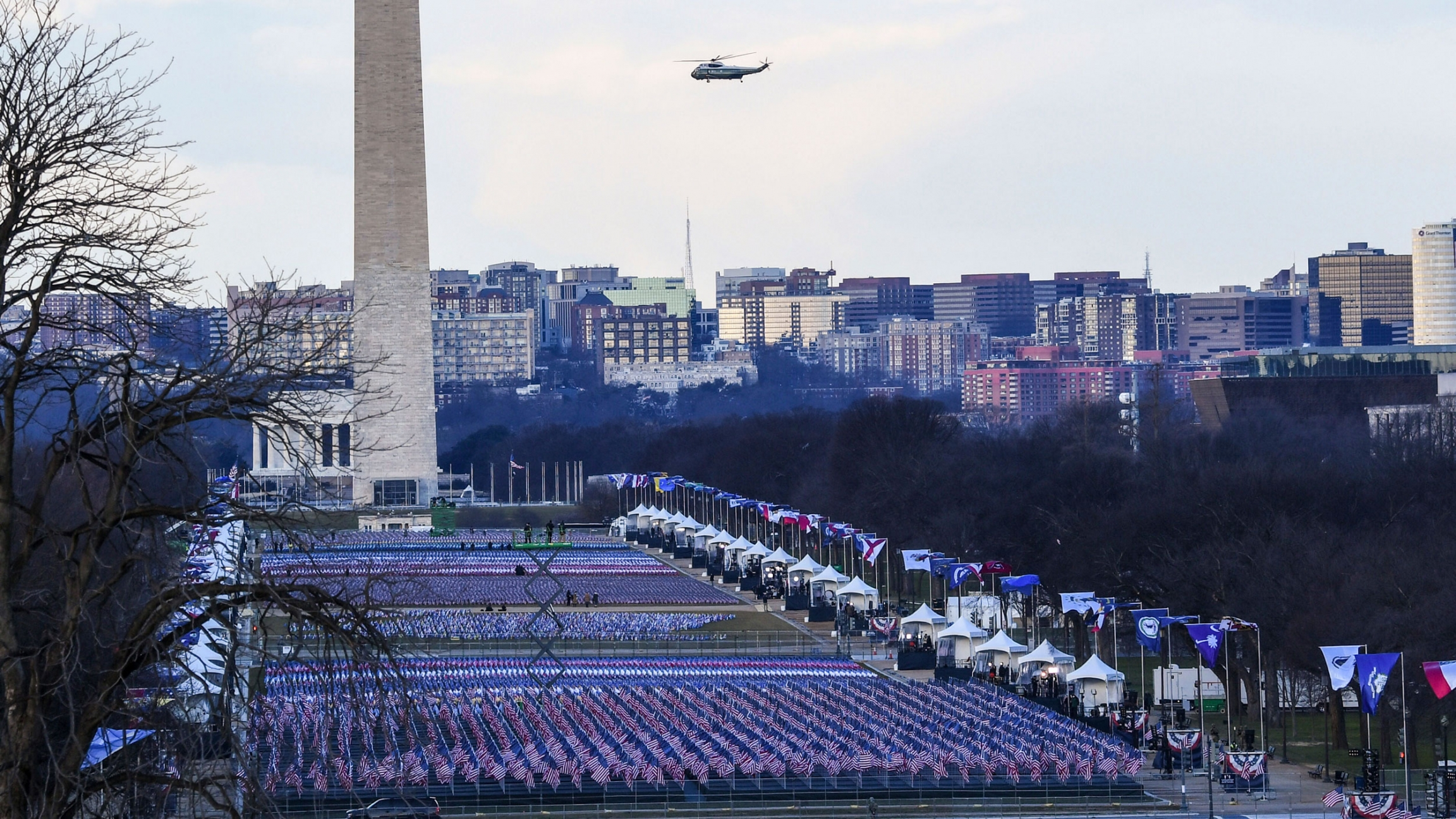 The US National Mall is shown covered in flags with the Washington Monument in the distance and the Marine One helicopter flying past.