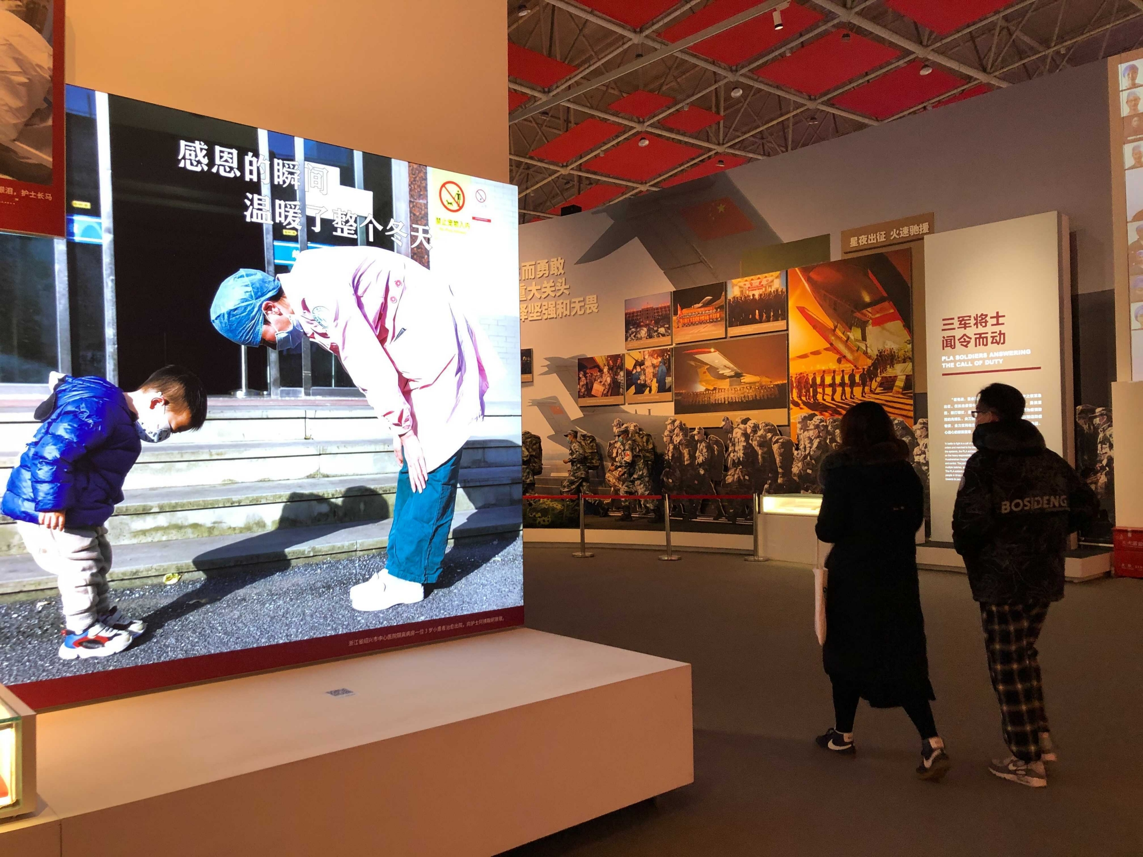 Visitors at the COVID-19 Exhibition in Wuhan, China, get a closer look at photos on display.