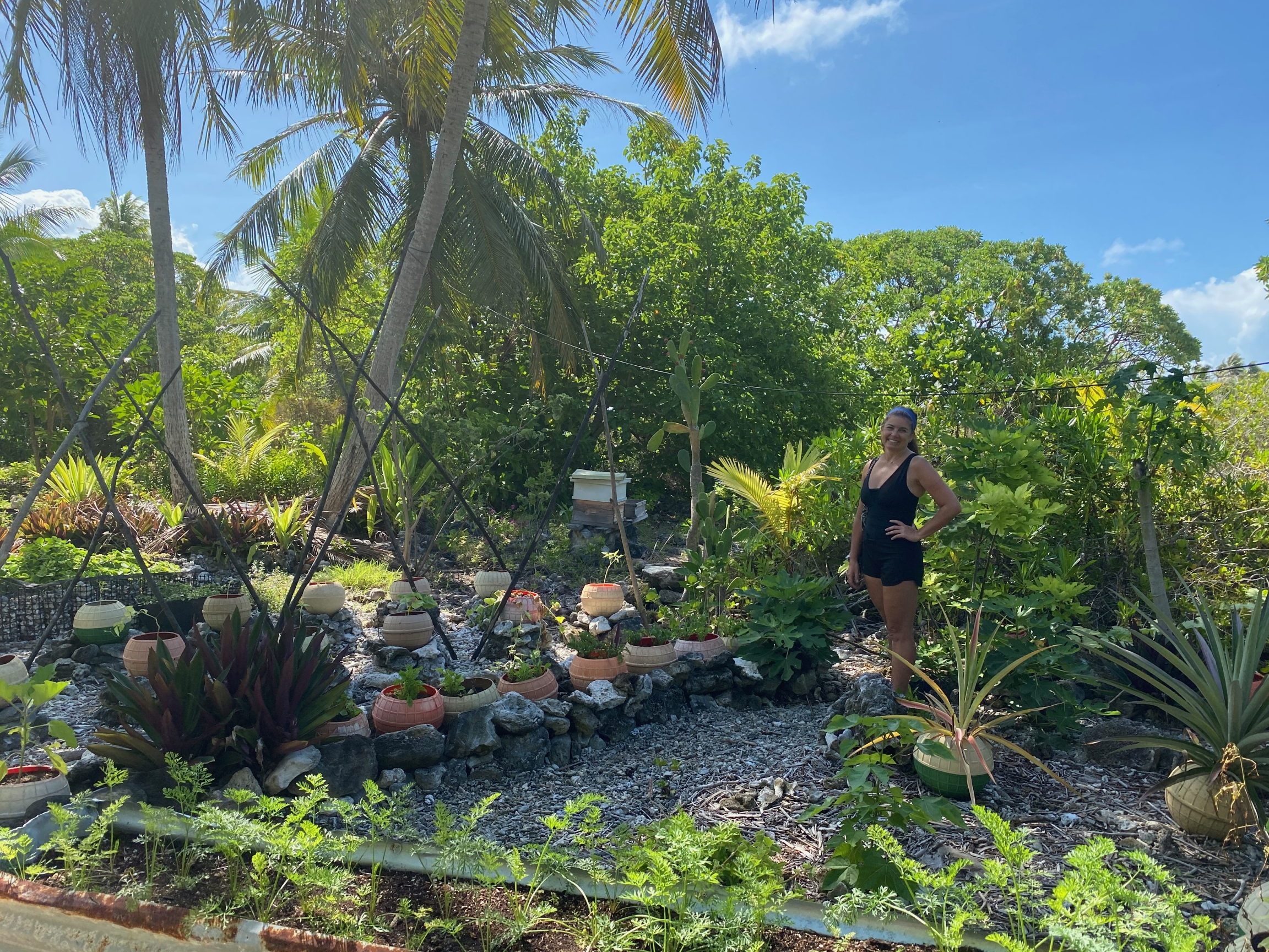 Kamoka Pearl co-owner Celeste Brash stands in front of a portion of the large garden that helps feedthe farm crew. In soil made from bird droppings and coconut husks, they're attempting to grow everything from arugula and pineapples to taro and carrots i