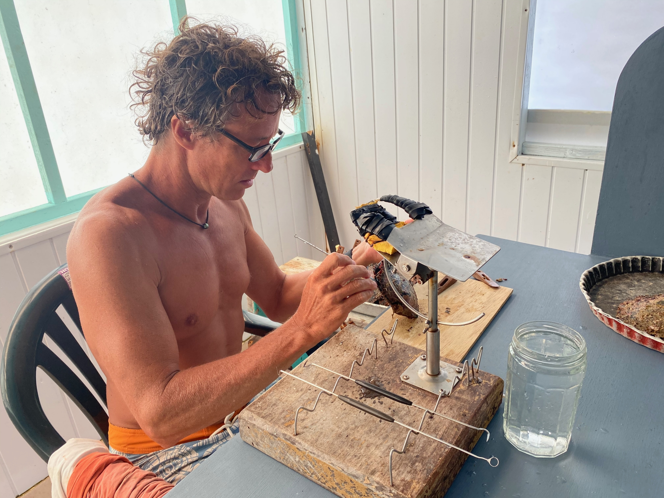 Kamoka Pearl Farm owner Josh Humbert uses a small spatula and scalpel to extract a cultured pearl from a newly cleaned oyster.