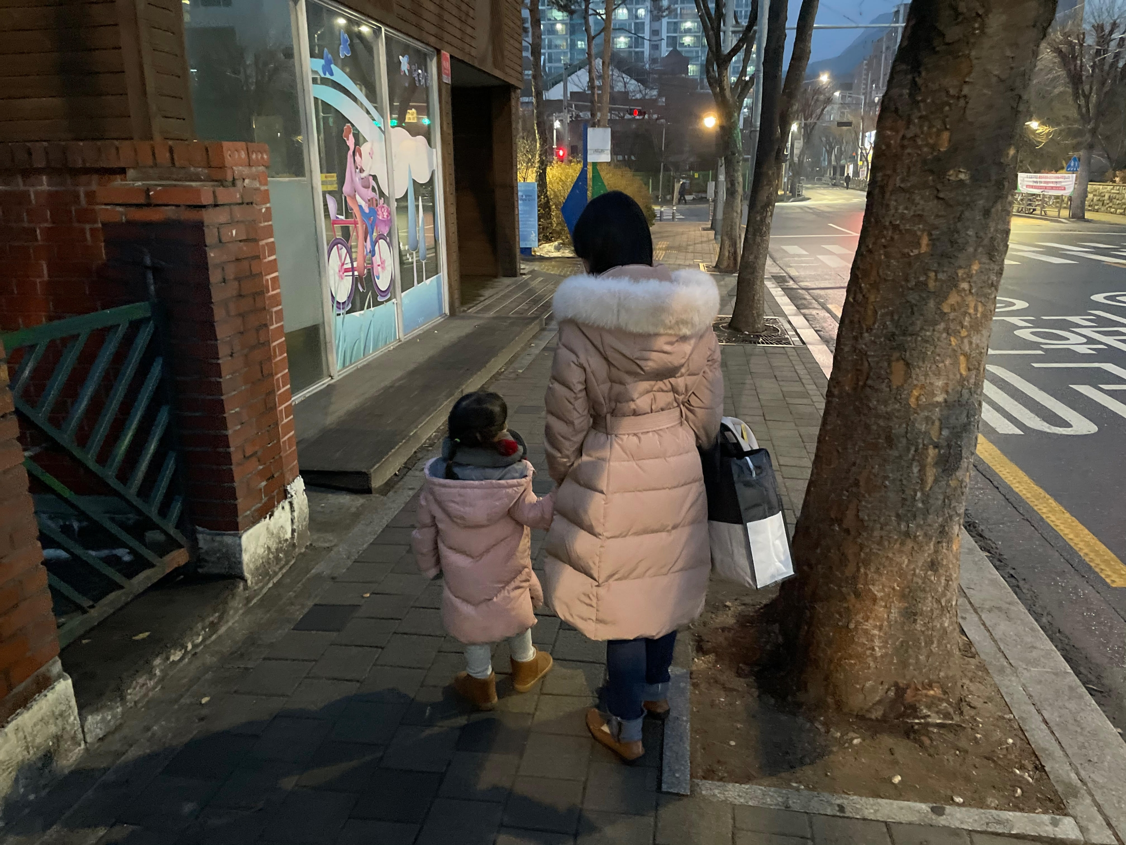 Kim, an advocate at the Korean Unwed Mothers Families' Association, a support group in Seoul, South Korea, walks with her daughter. She asked that her full name not be used due to the stigma associated with being a single mother.