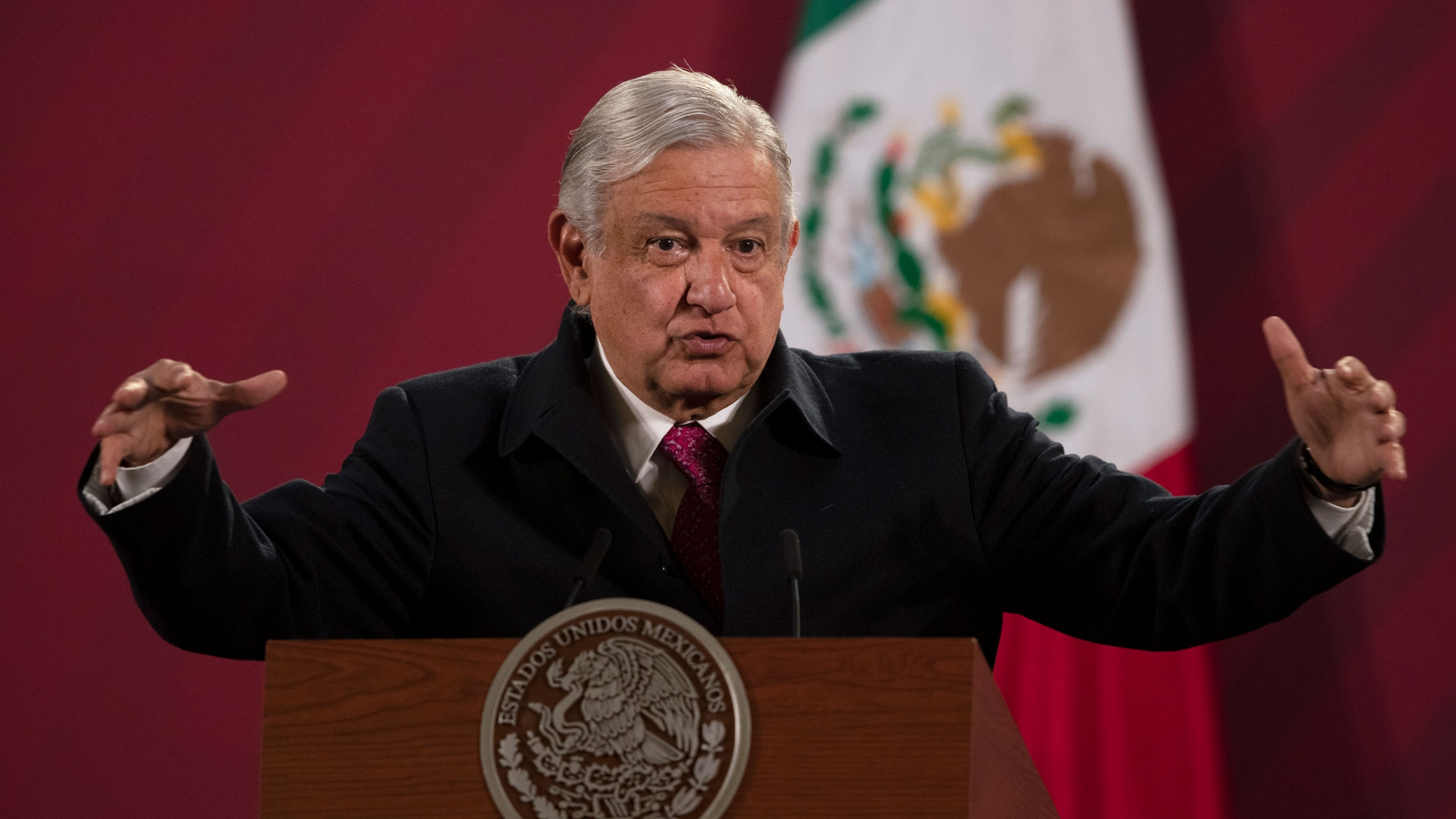Mexican President Andrés Manuel López Obrador is shown speaking while standing behind a podium with his arms outstretched.
