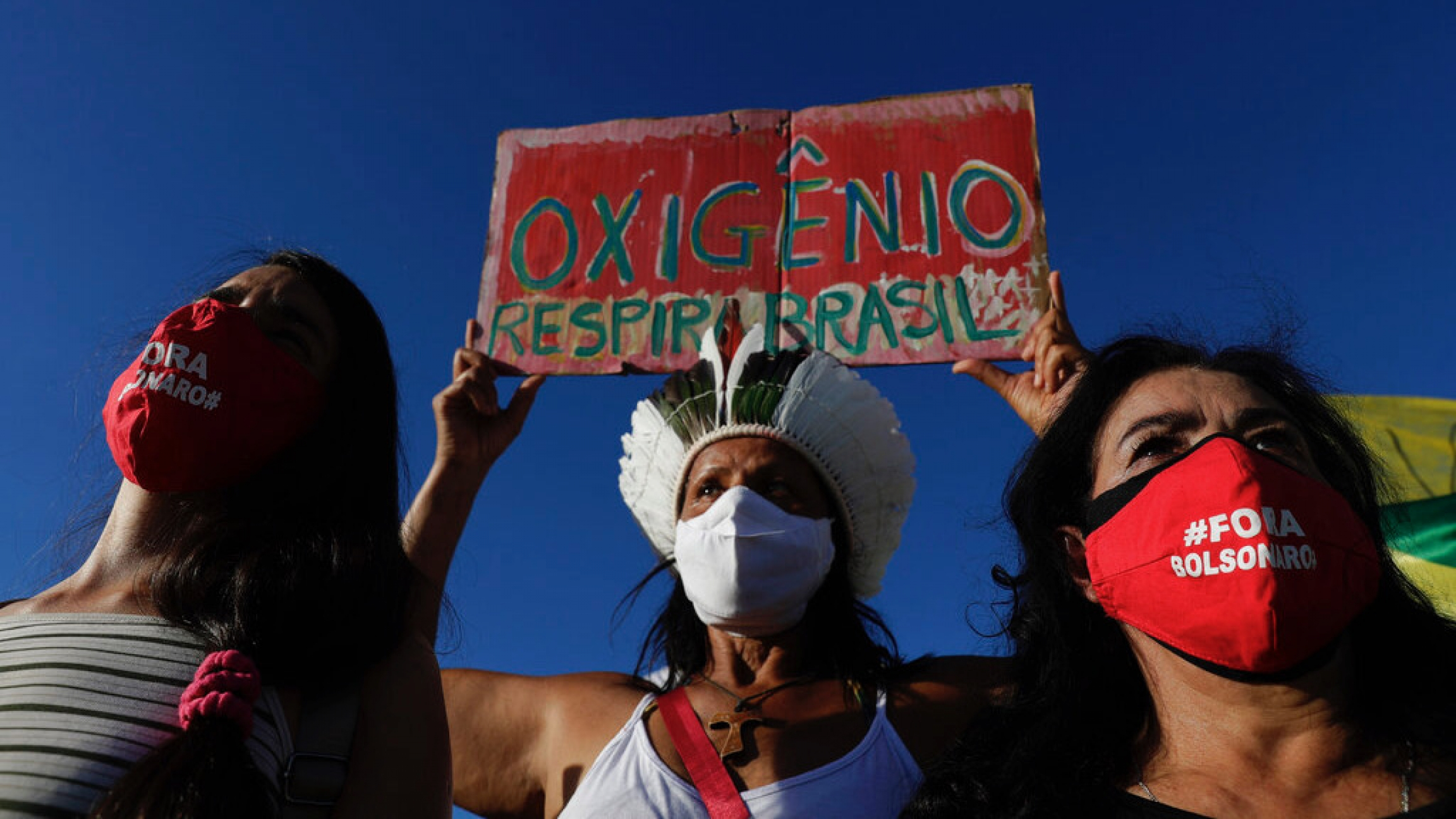 "Demonstrators wearing masks with text written in Portuguese that read ""Bolsonaro out,"" and a sign with the phrase ""Oxygen, Breathe Brazil,"" protest against the government's response in combating COVID-19 and demanding the impeachment of Brazil's President"