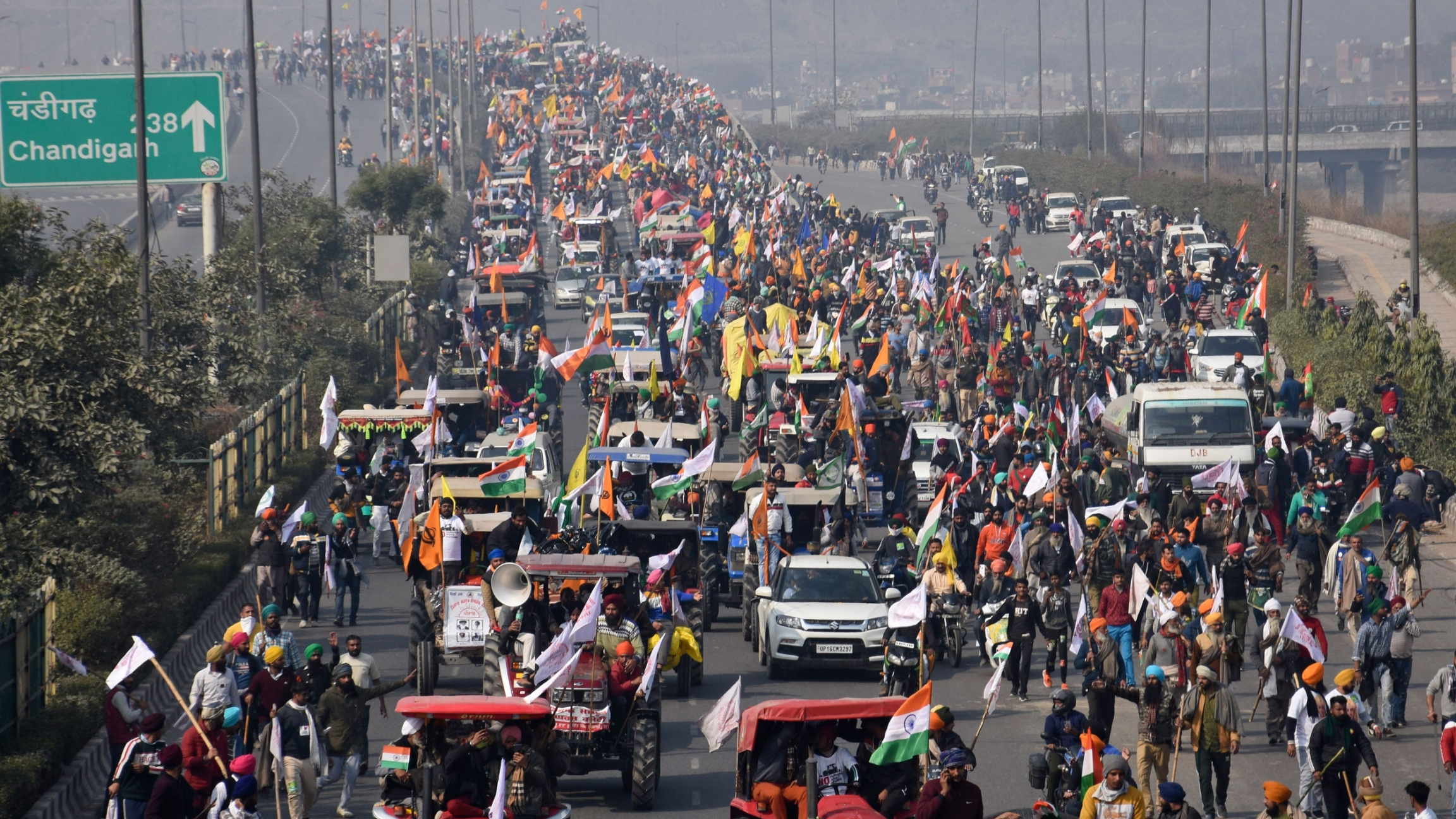 A multiple lane road is shown filled with protesters driving tractors and other vehicles with thousands of people shown all over the road.