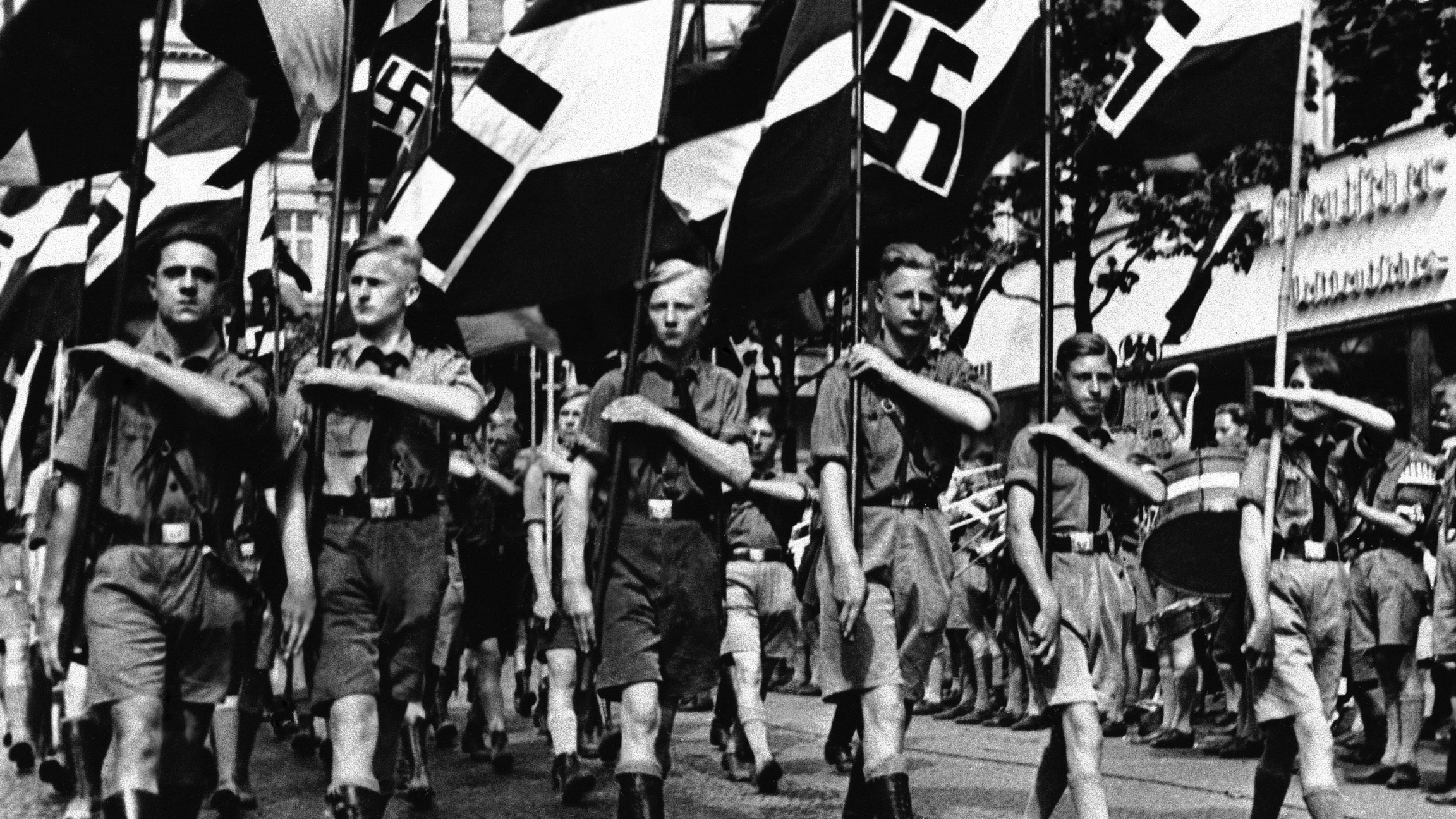 Adolf Hitler's Nazi campaign includes the indoctrination of children in Berlin, Feb. 24, 1936. The boys are trained for future military service and the girls to be obedient hausfraus. Here a group of boys proudly march beneath Nazi standards.