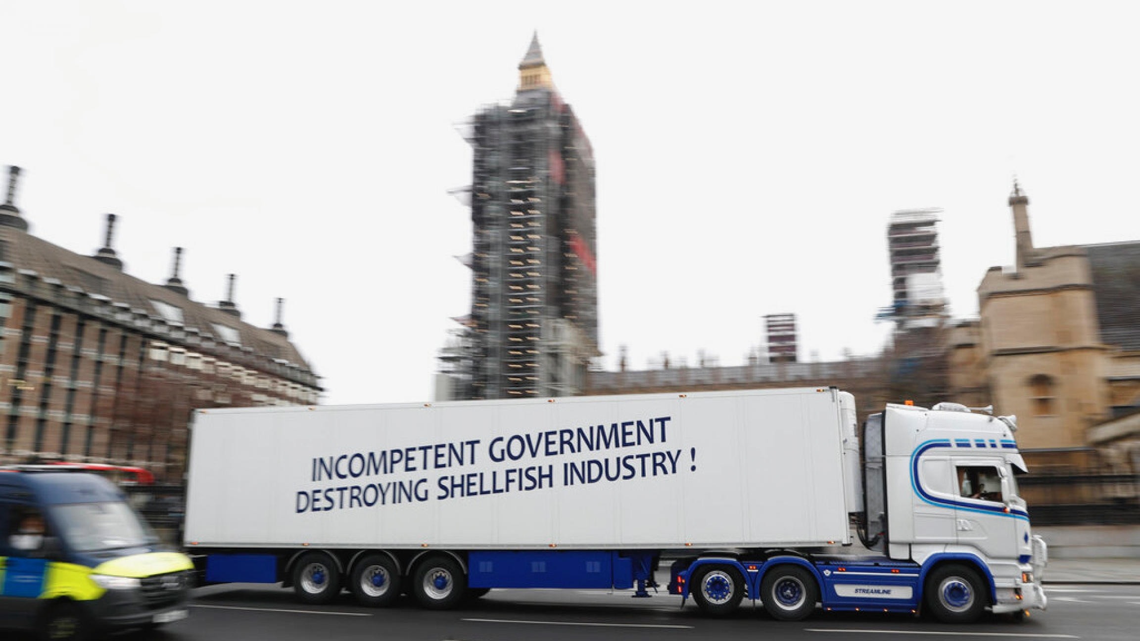 "A shellfish export truck with a protest sign written across the trailer ""Incompetent Government Destroying Shellfish Industry"" drives past the Palace of Westminster in London"