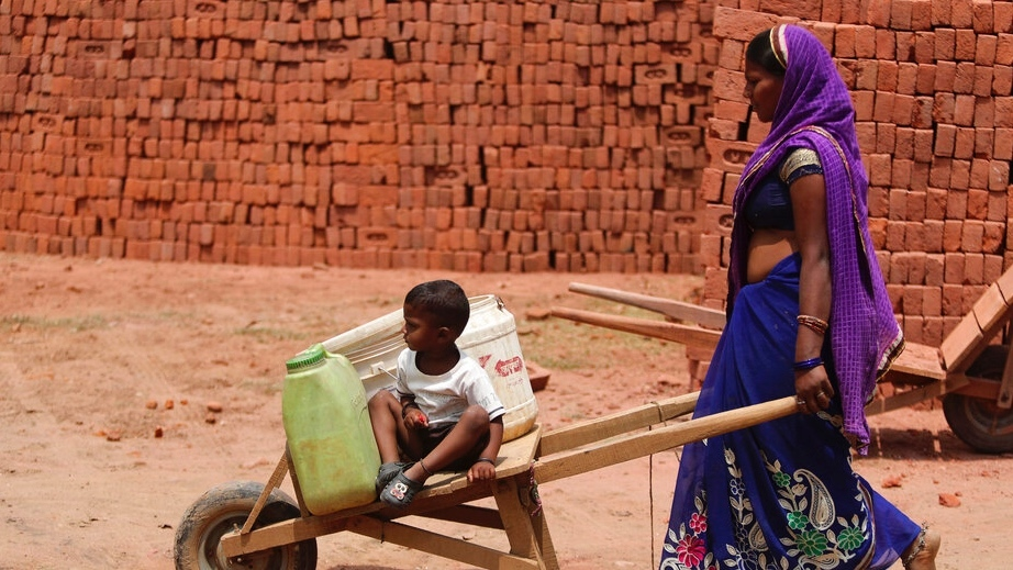 A woman pushes a wheelbarrow with a child riding on it.