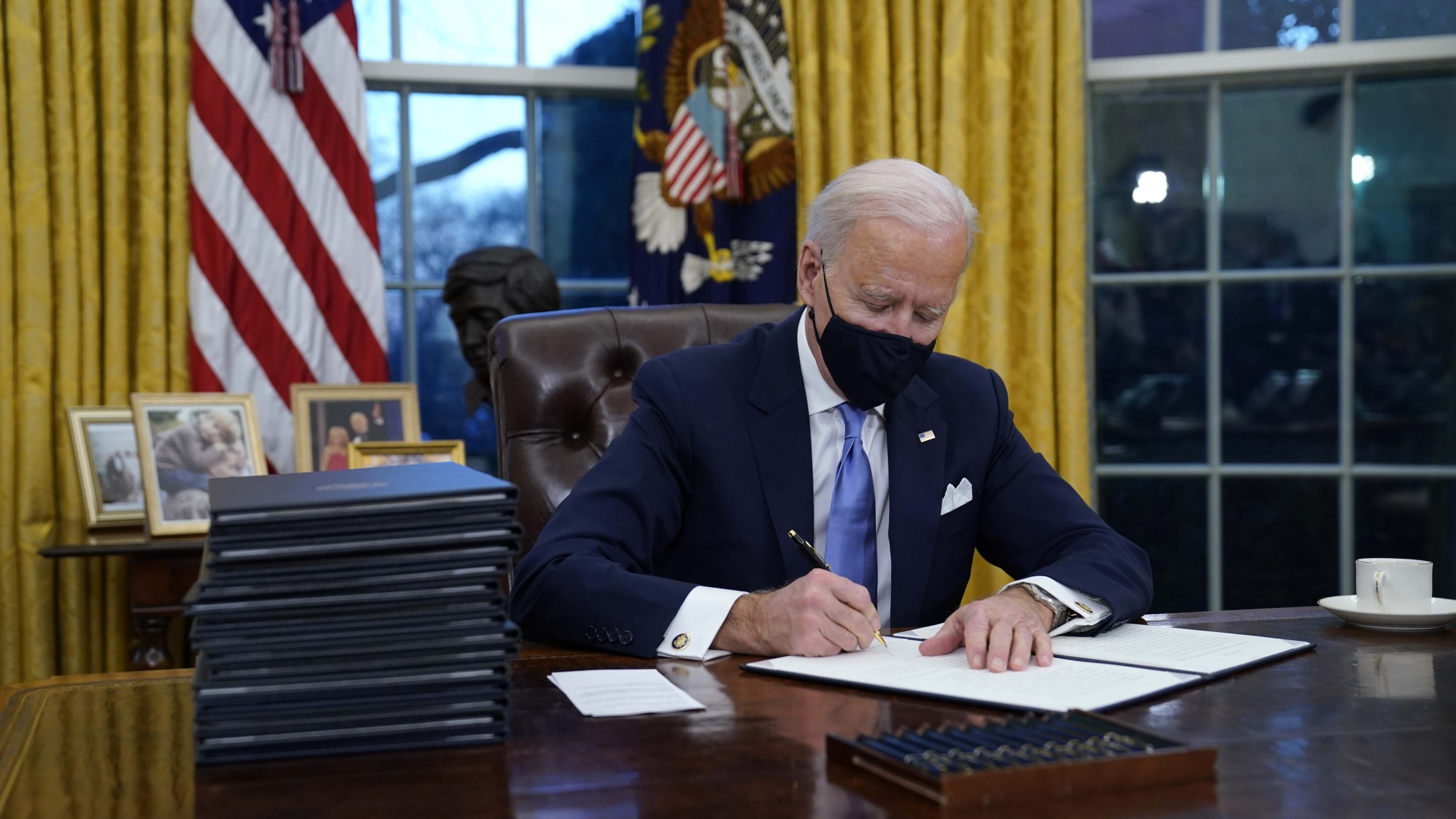 President Joe Biden signs his first executive order in the Oval Office of the White House on Jan. 20, 2021, in Washington, DC.