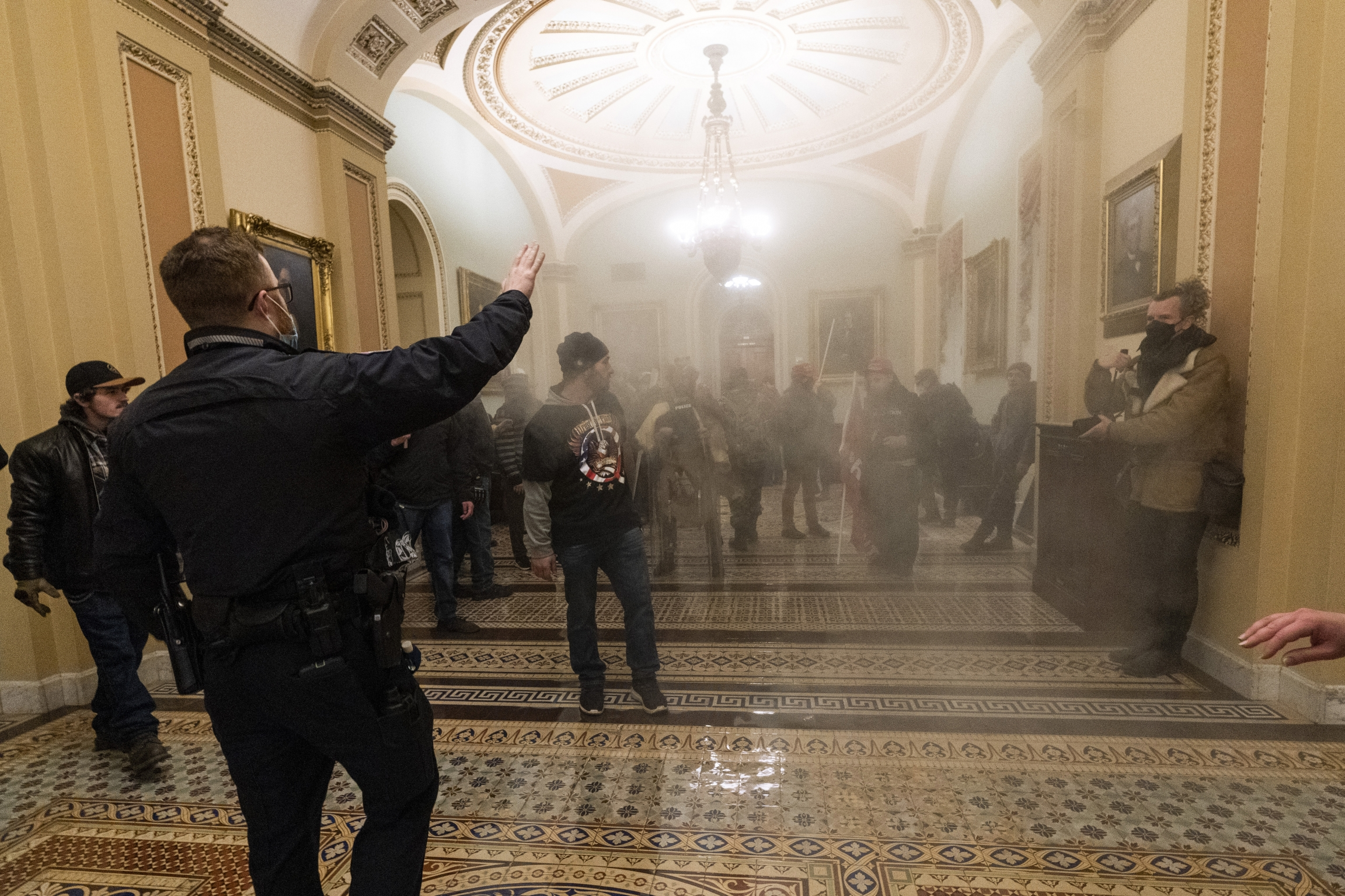 Smoke fills the walkway outside the Senate Chamber as supporters of President Donald Trump are confronted by US Capitol Police