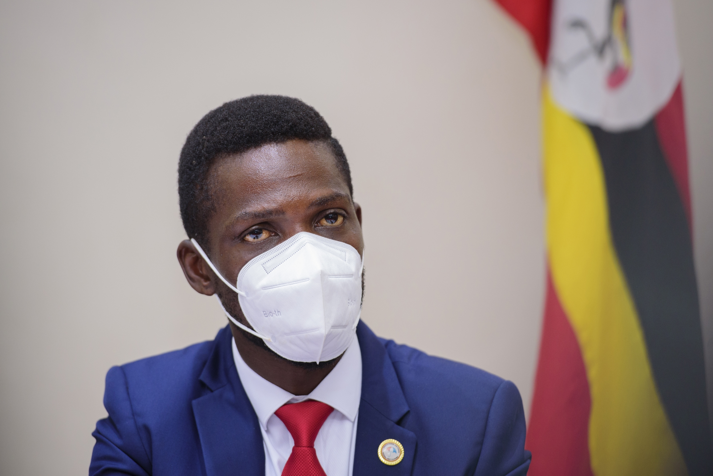 Bobi Wine, during a press conference in Kampala Uganda, Tuesday, Jan.12, 2021, wears a white face mask and blue suit with red tie.