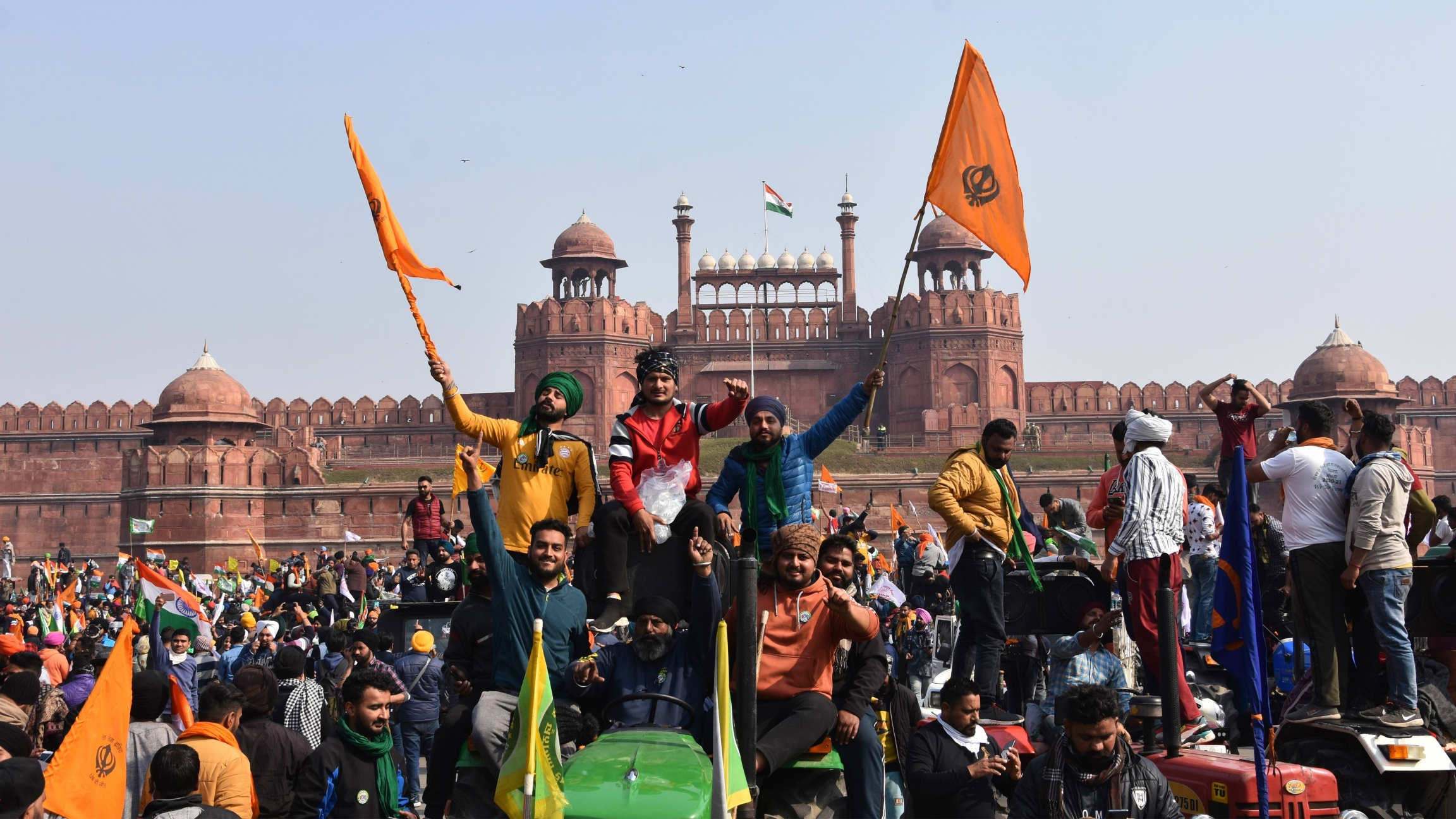 Sikhs wave the Nishan Sahib, a Sikh religious flag, as they arrive at the historic Red Fort monument in New Delhi, India, on Tuesday, Jan. 26, 2021.