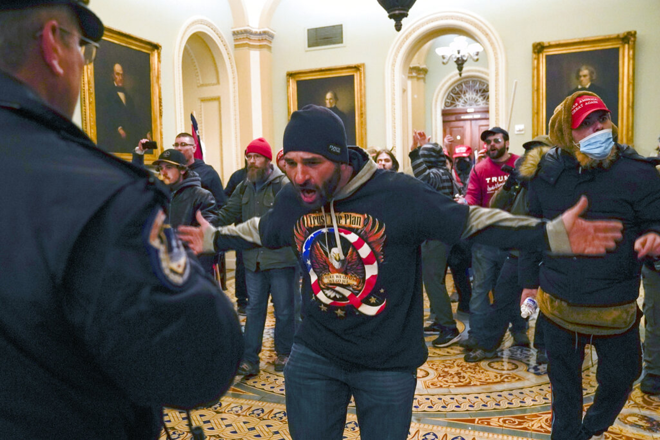Trump supporters gesture to US Capitol Police in the hallway outside of the Senate chamber at the Capitol in Washington, Jan. 6, 2021.