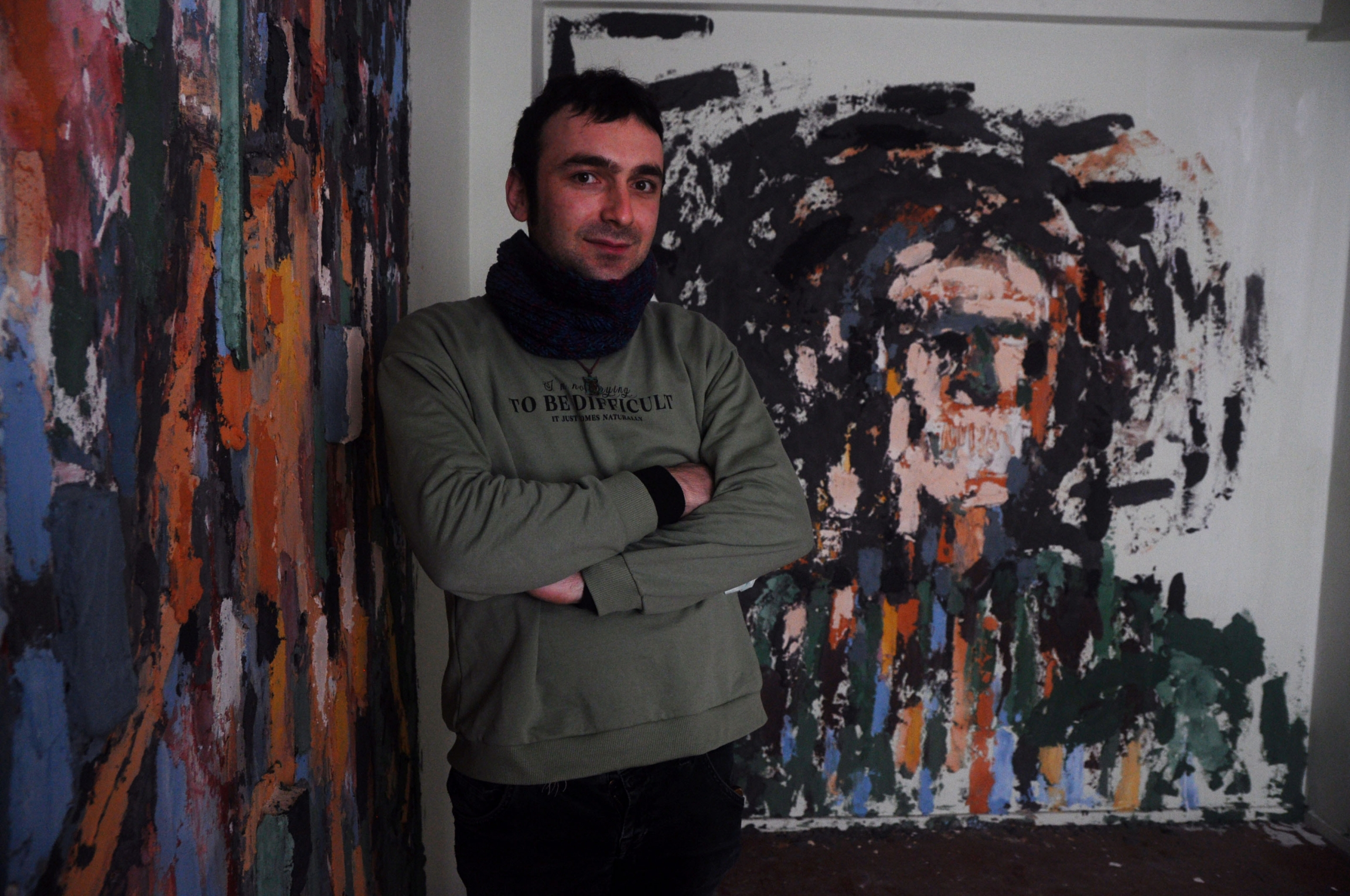 "Batikan Bostanci, 30, stands with his installation, ""Powerless Faces."" Bostanci layered pigments and paint over textured concrete, wood and plastic remnants found in the debris left by the building's residents."