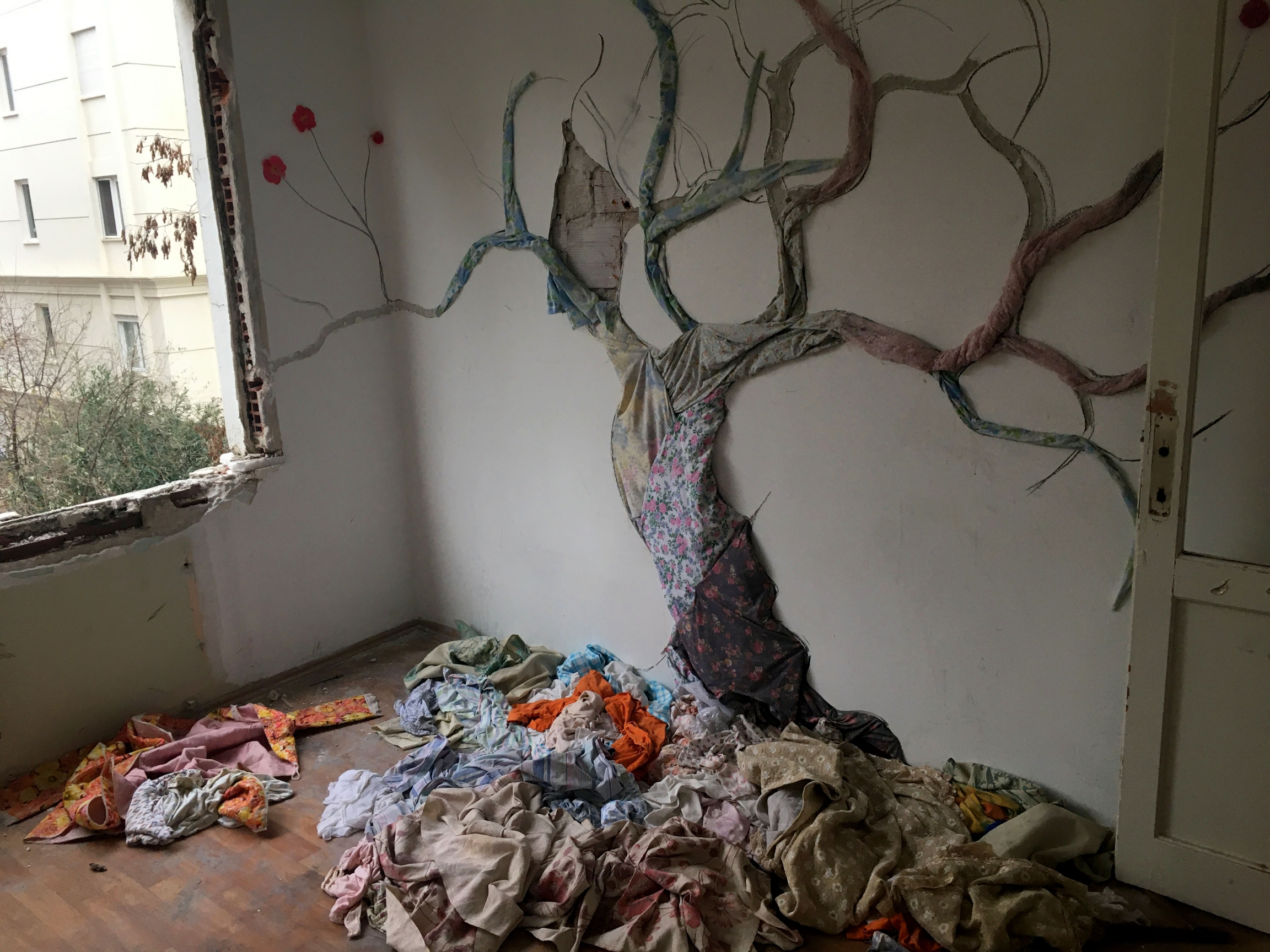 A tree made of found fabrics pinned to a wall by Songul Girgin gazes wistfully out of what was once a bedroom window.