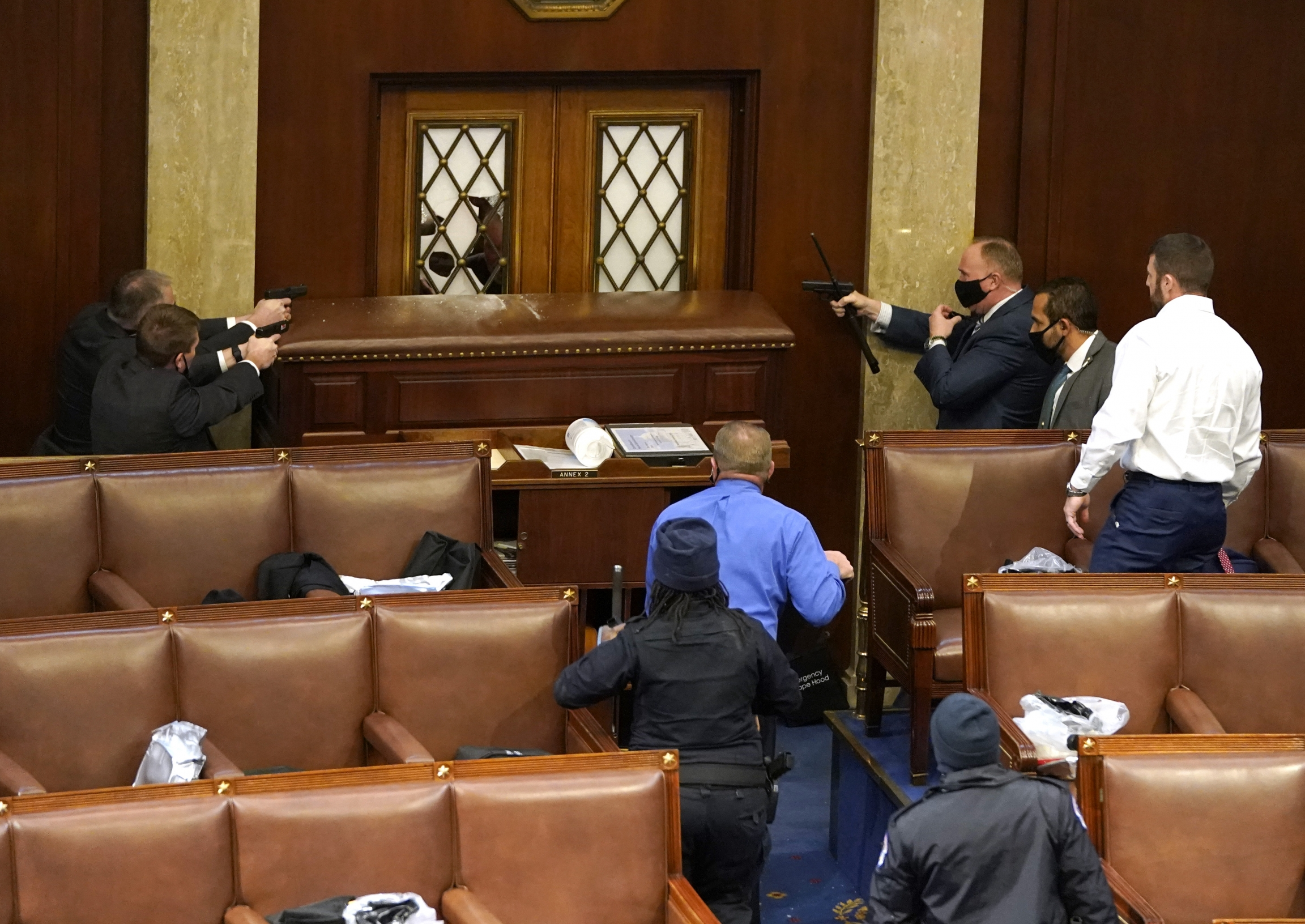 US Capitol police officers point their guns at a door that was vandalized in the House Chamber during a joint session of Congress on Jan.06, 2021, in Washington, DC.