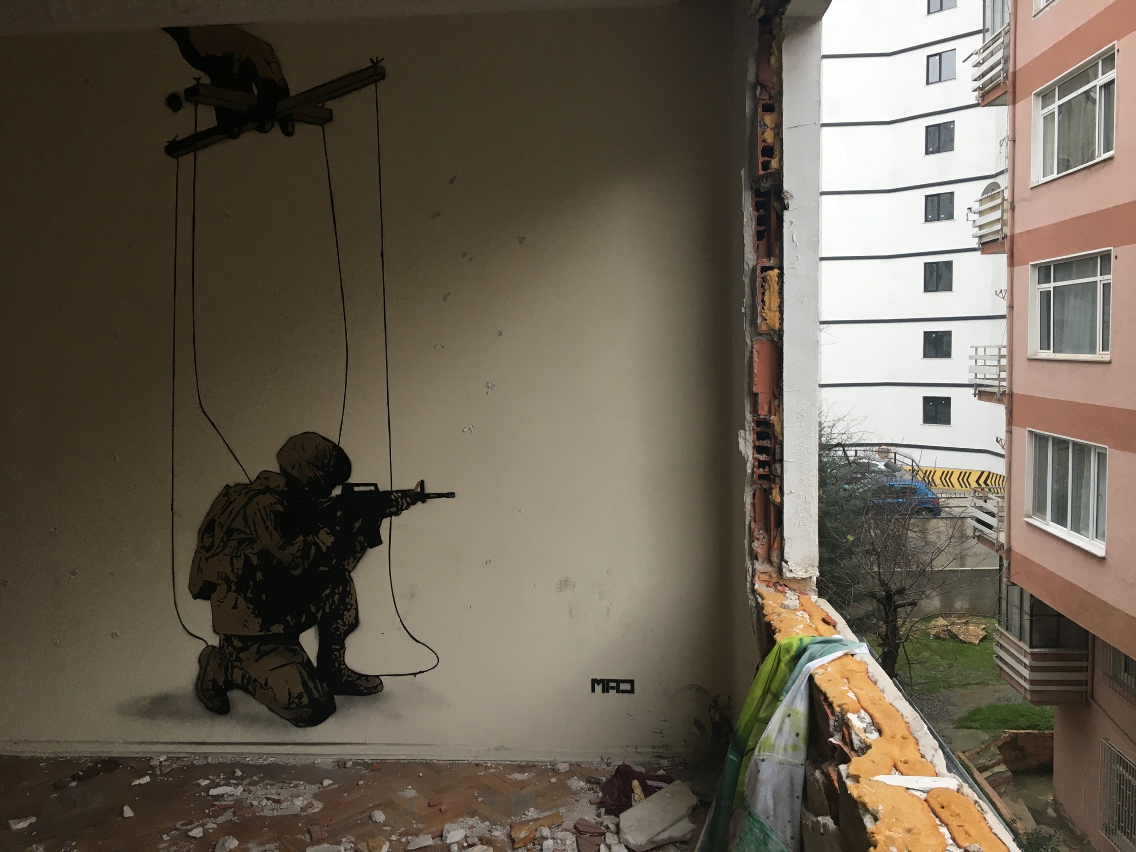 """Stencil artist MAD, from Tabriz, Iran, contributed a floor-to-ceiling image of a sniper aiming a gun, tied to puppet strings. He calls the piece """"Hidden Reality."""""""