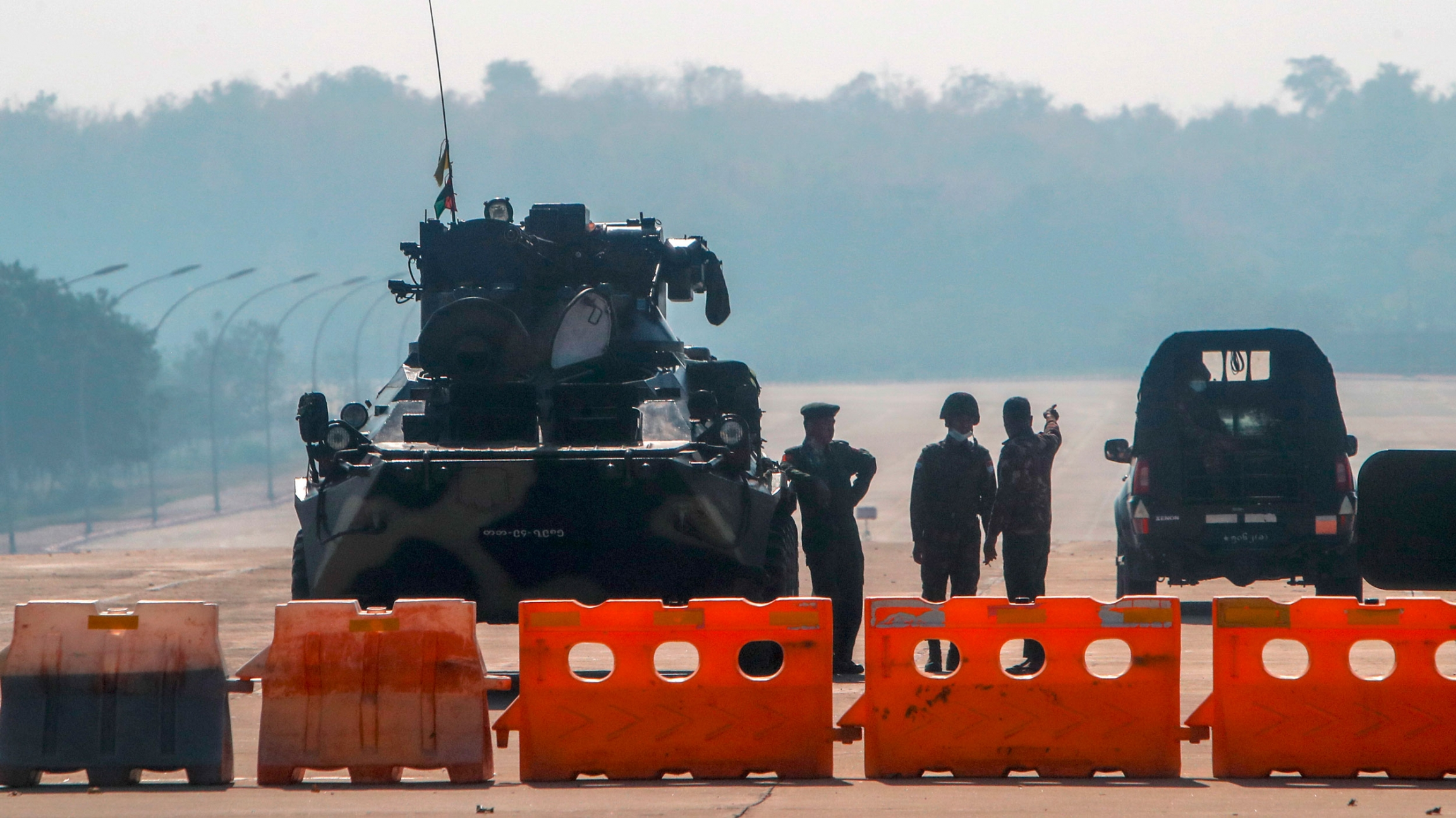 Several military personale are shown standing next to a tank with orange road blocks lined up across as road.