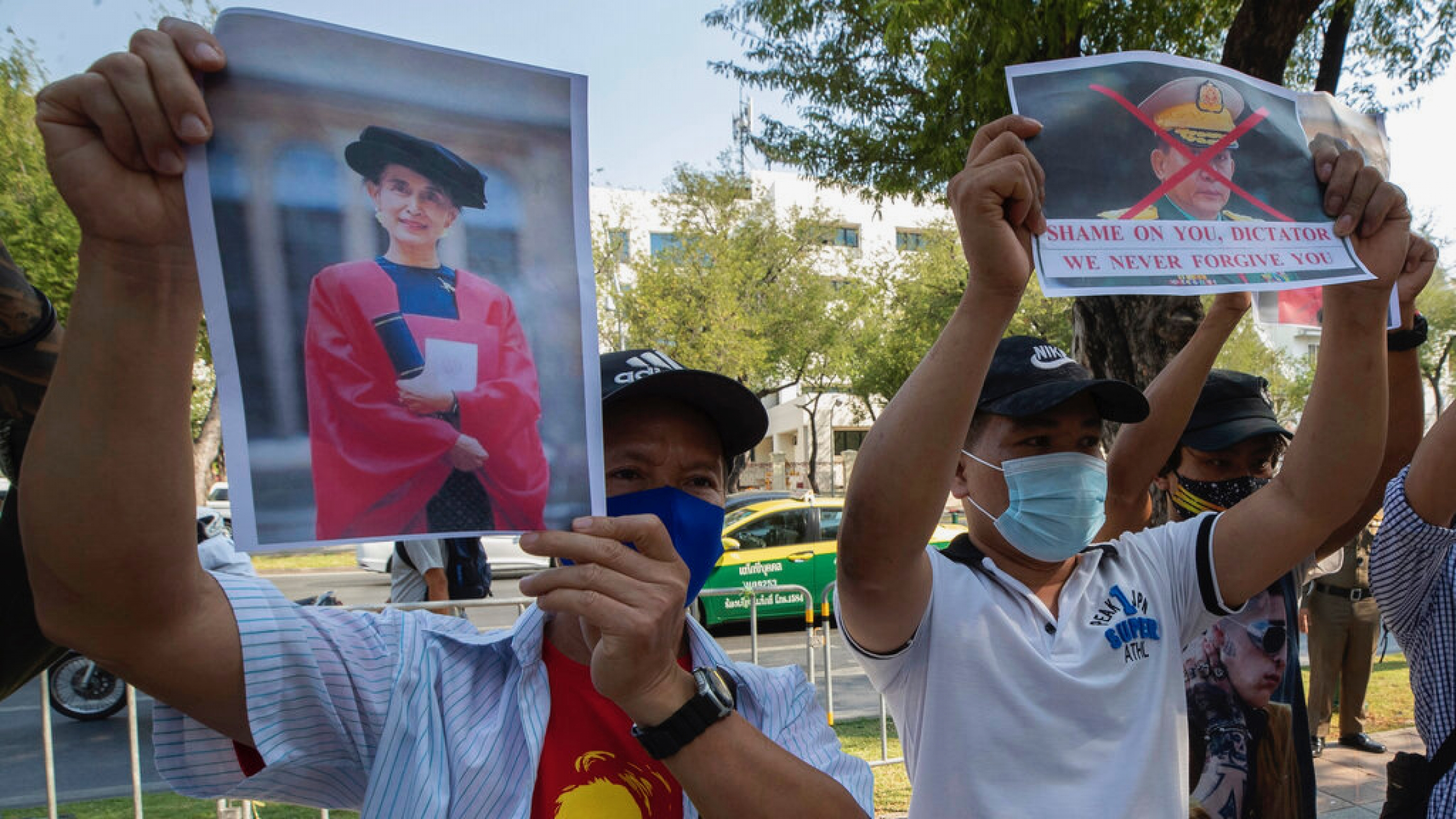 Myanmar nationals living in Thailand hold pictures of Myanmar leader Aung San Suu Kyi and Myanmar military Commander in Chief Senior Gen. Min Aung Hlaing during a protest in front of the United Nations building in Bangkok, Feb. 3, 2021.