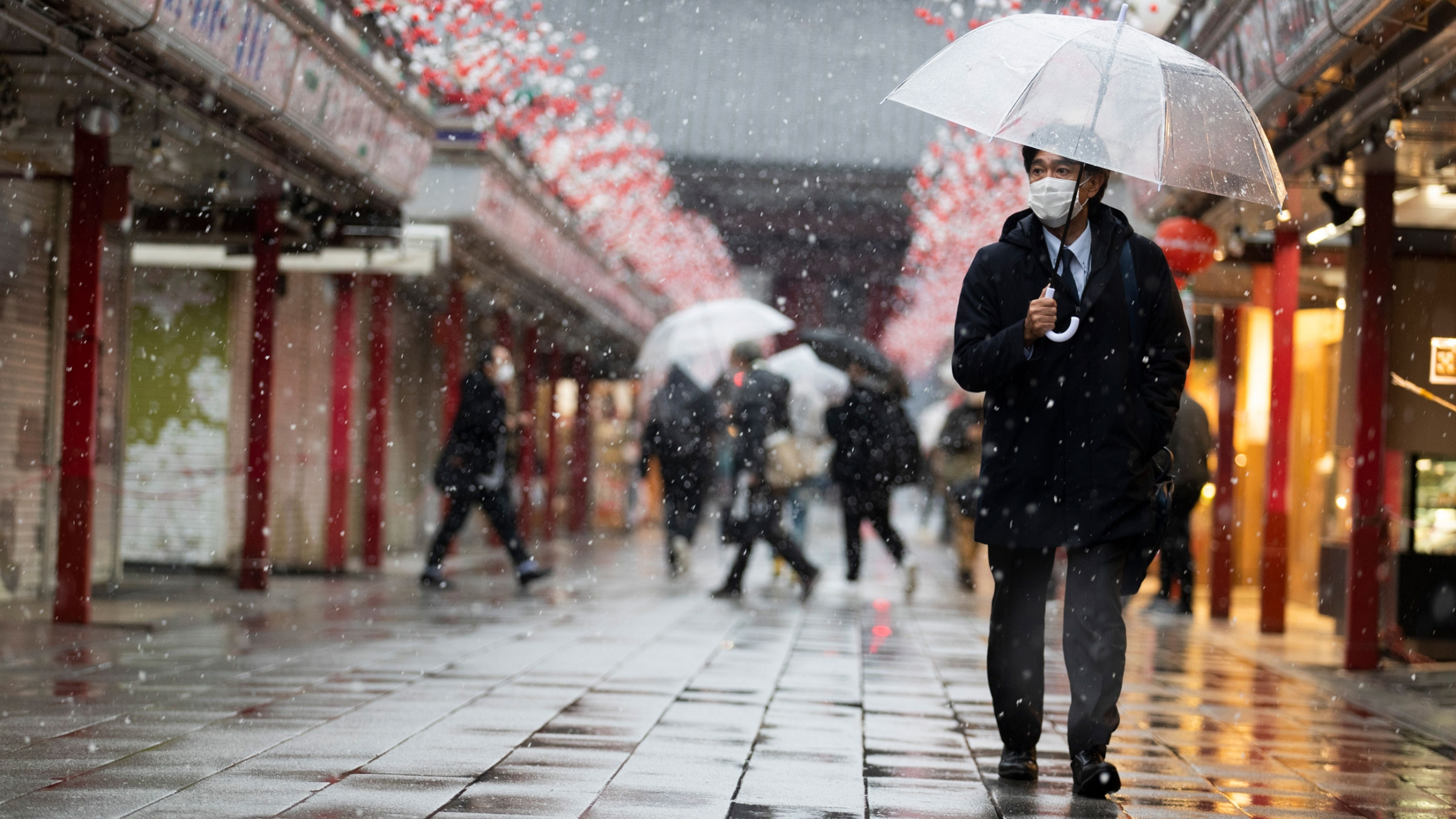 A man is shown carrying a clear umbrella and wearing a face mask while walking with his left hand in his pocket.