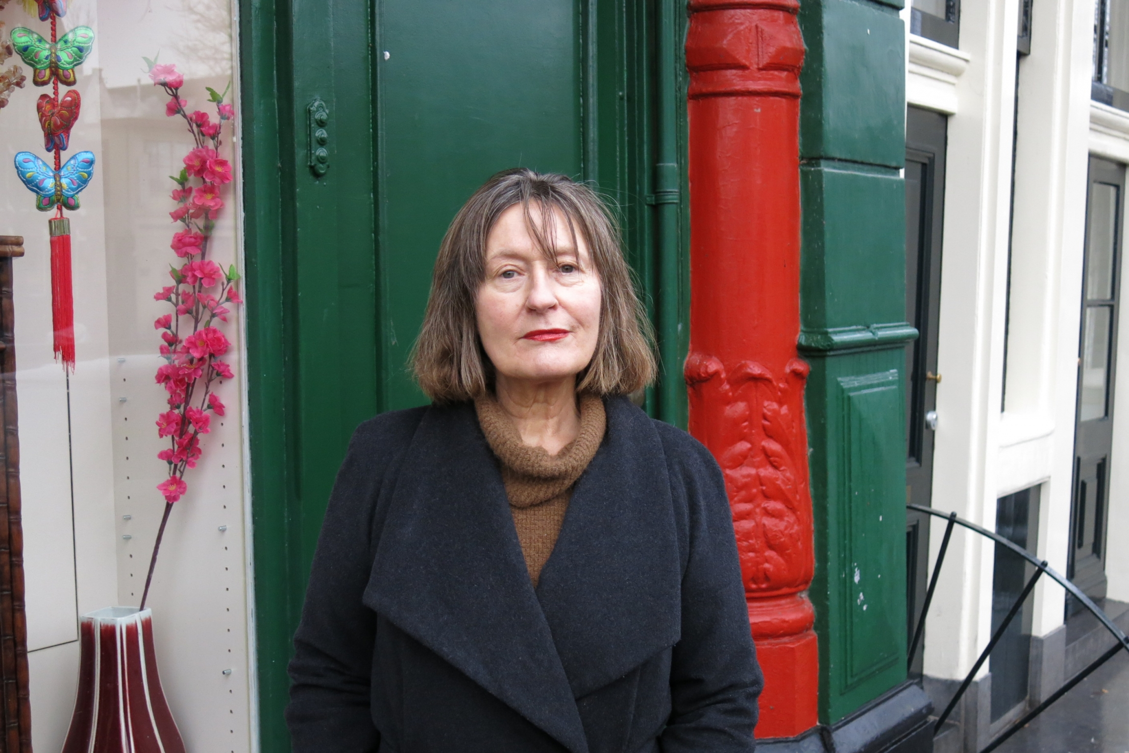 A woman stands before a green door with a red-painted pillar.
