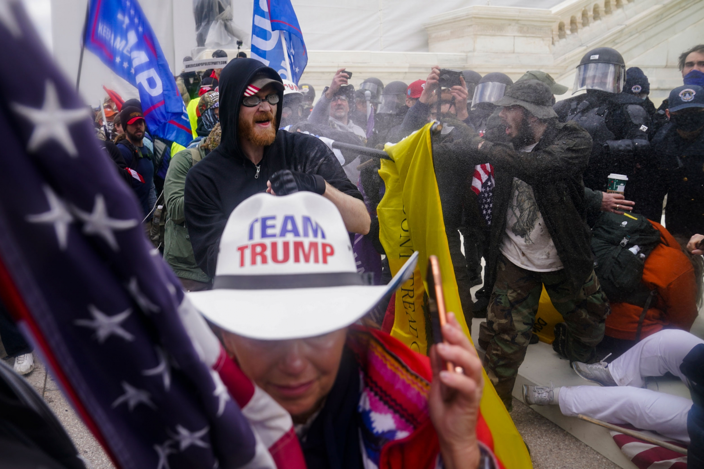 Several people wearing pro-Trump paraphernalia are shown outside of the US Capitol building with police wearing helmet and face guards shown opposite.