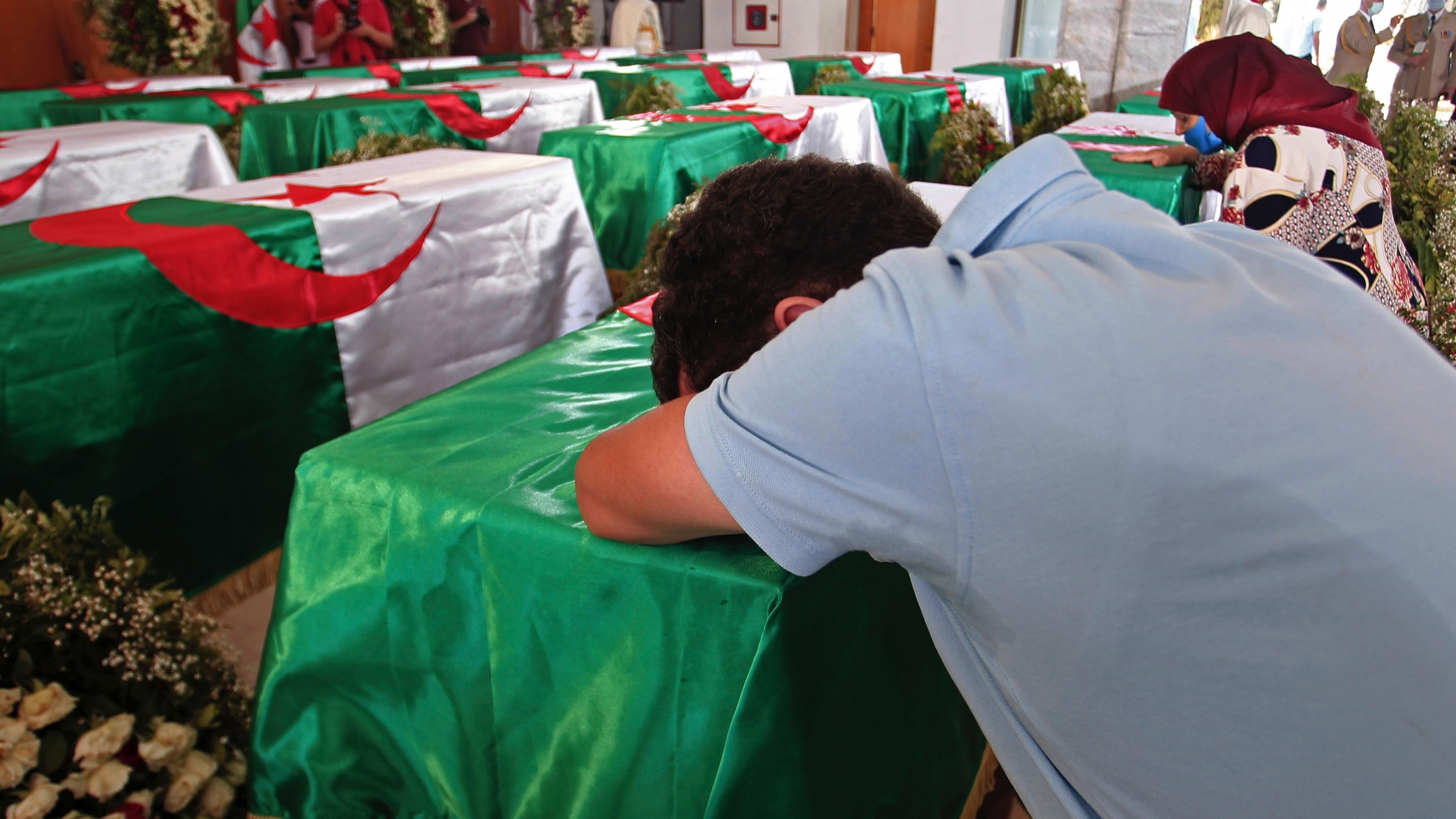 A man wearing a blue shirt leans his body over a coffin draped with the Algerian flag in a room full of coffins.