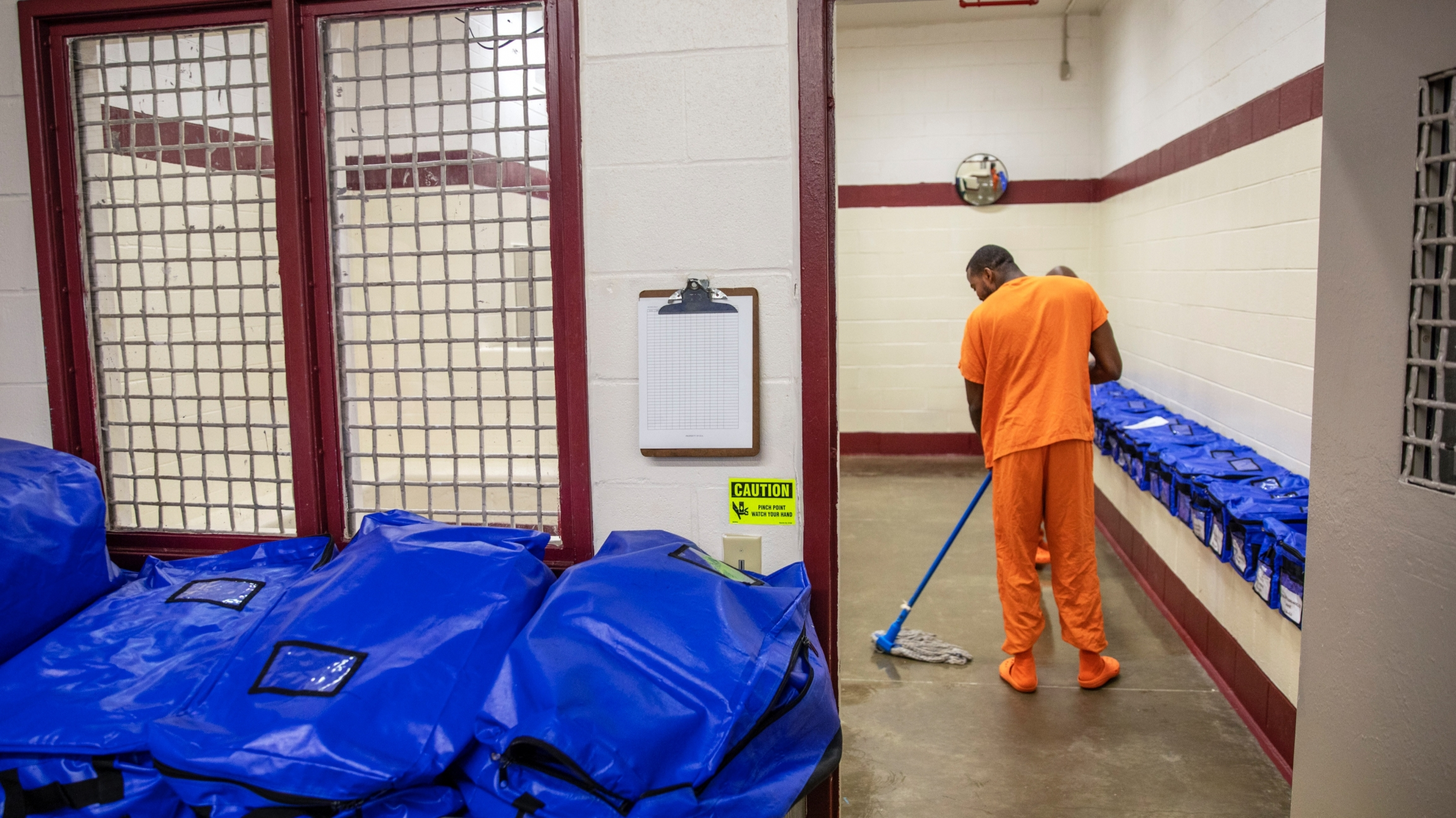 An inmate wearing an orange suit mops near blue plastic bags inside a detention center.