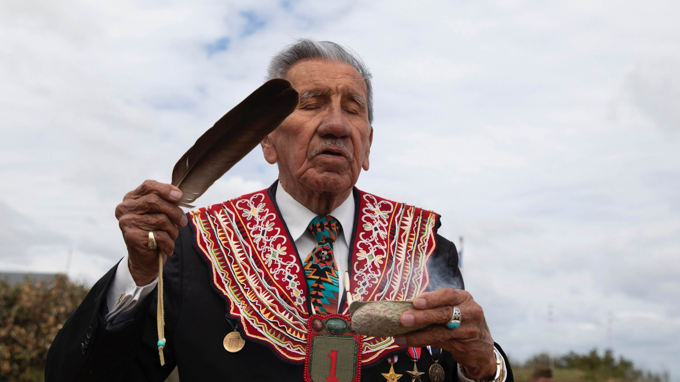 A Native American elder performs a ritual ceremony using a feather.