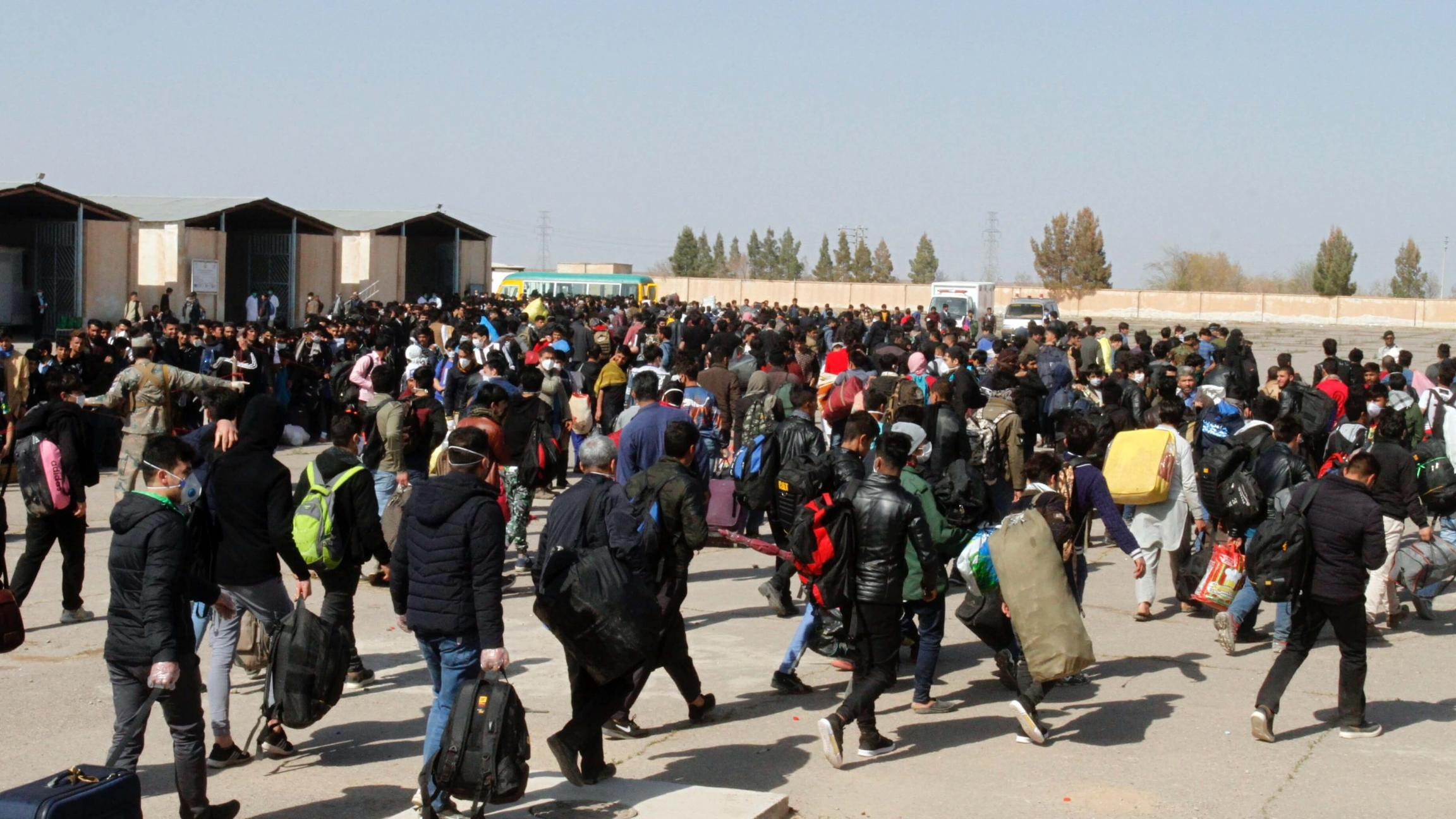 A large group of refugees walk through an Afghanistan-Iran border point.