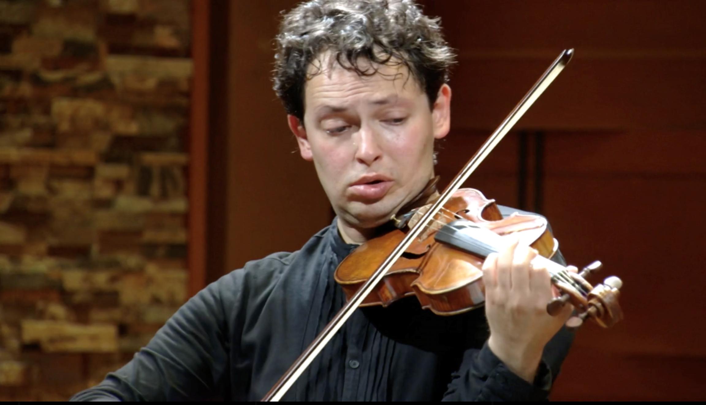 A man holds a violin