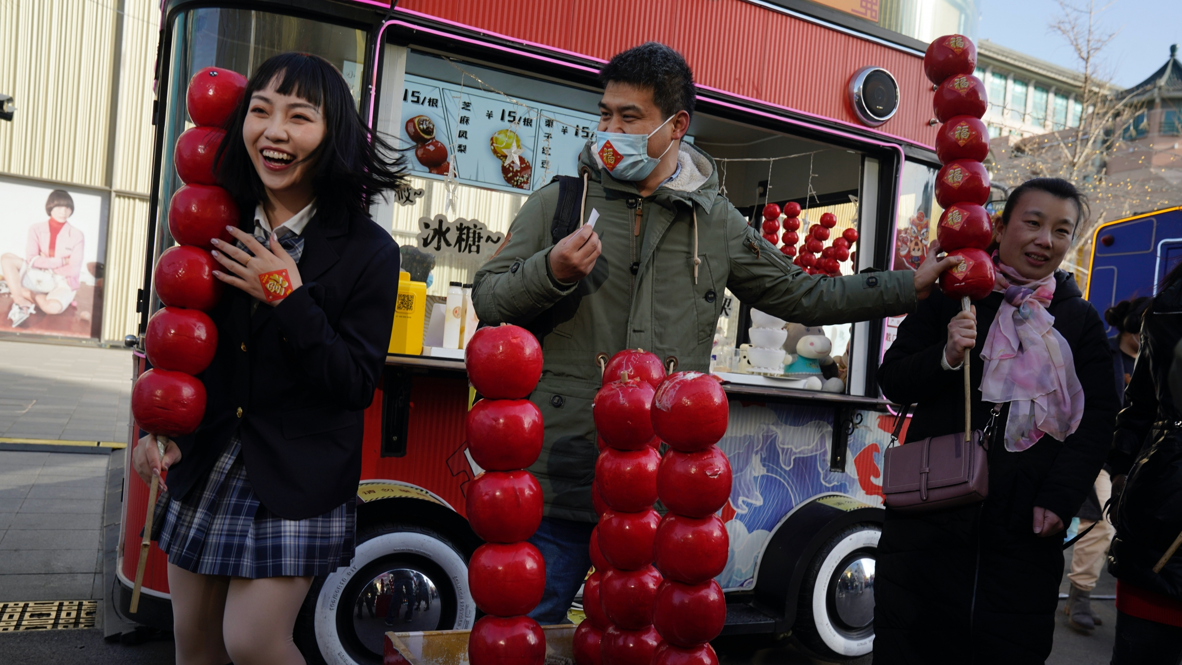 A Chinese woman reacts as she holds a giant replica of candy haw, a popular Beijing snack, at a street stall near Wangfujing on the fourth day of the Lunar Chinese New Year in Beijing on Feb. 15, 2021.